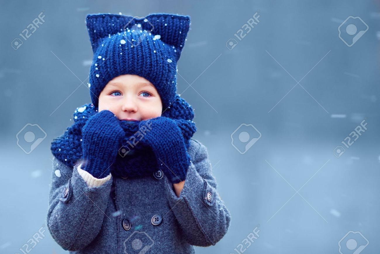 かわいい男の子、雪の中を歩いて冬の服の子供 ロイヤリティーフリー
