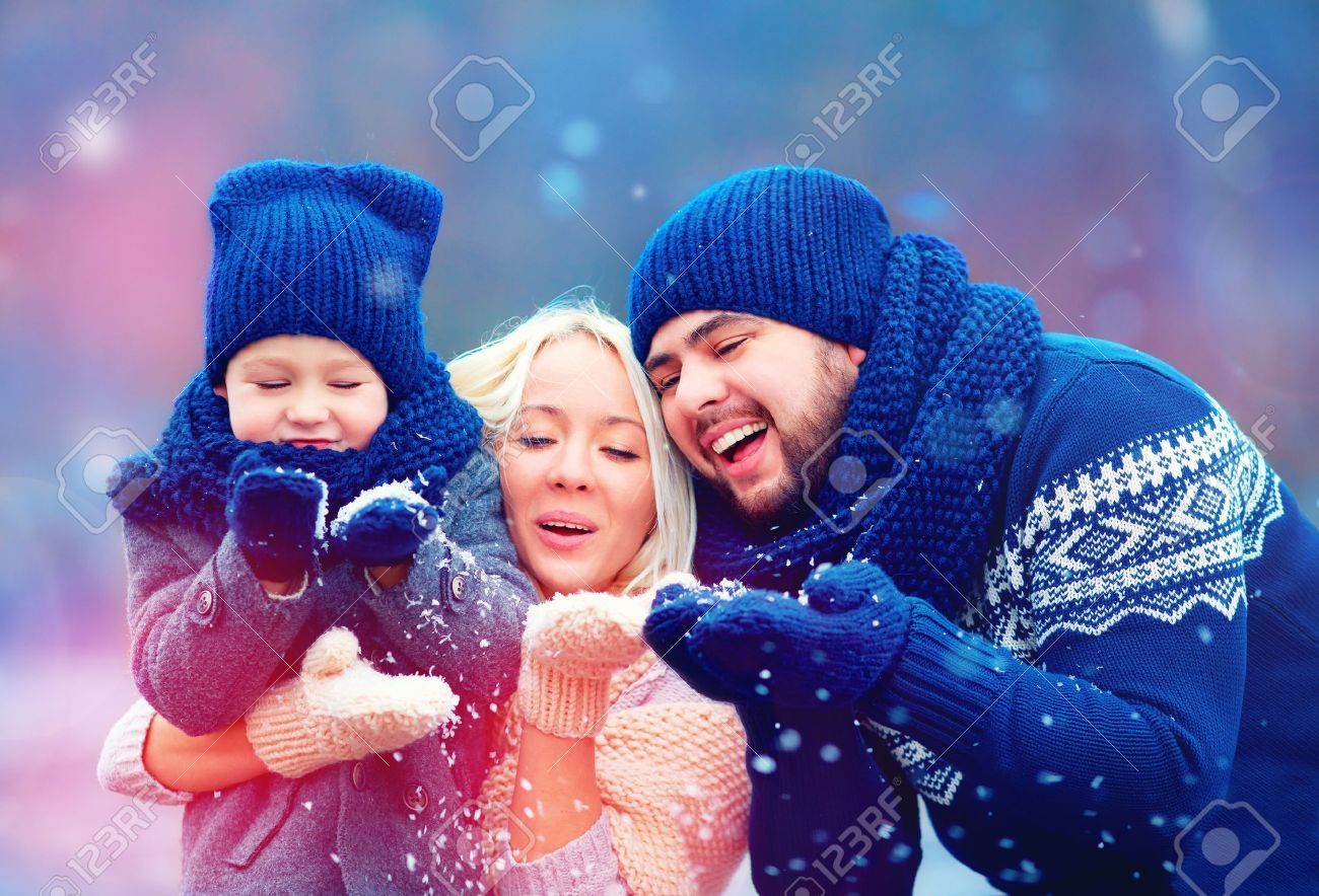 portrait of happy family blowing winter snow - 50356780