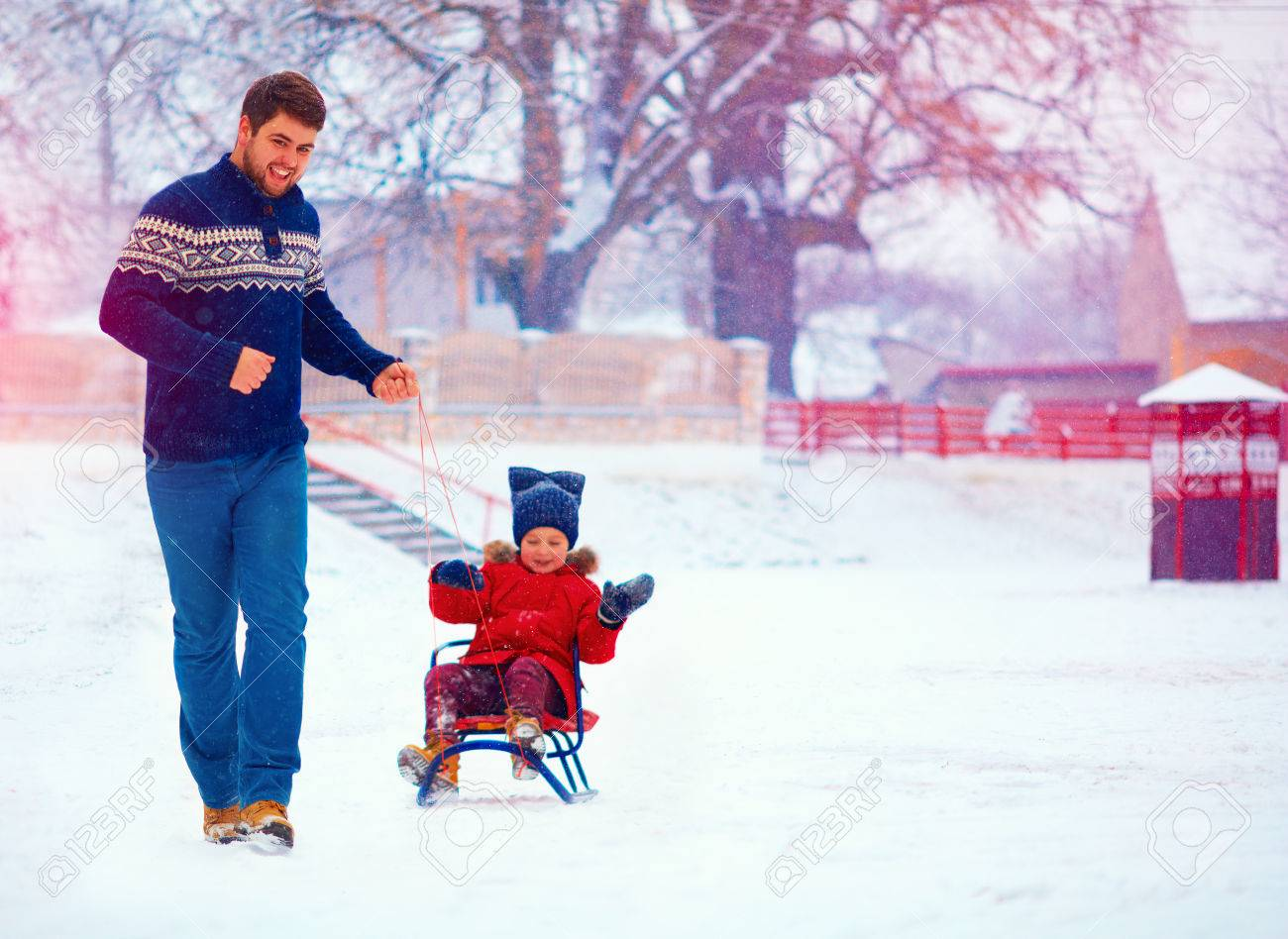 eda2d85a4a happy father and son having fun with sledge under winter snow Stock Photo -  50965462