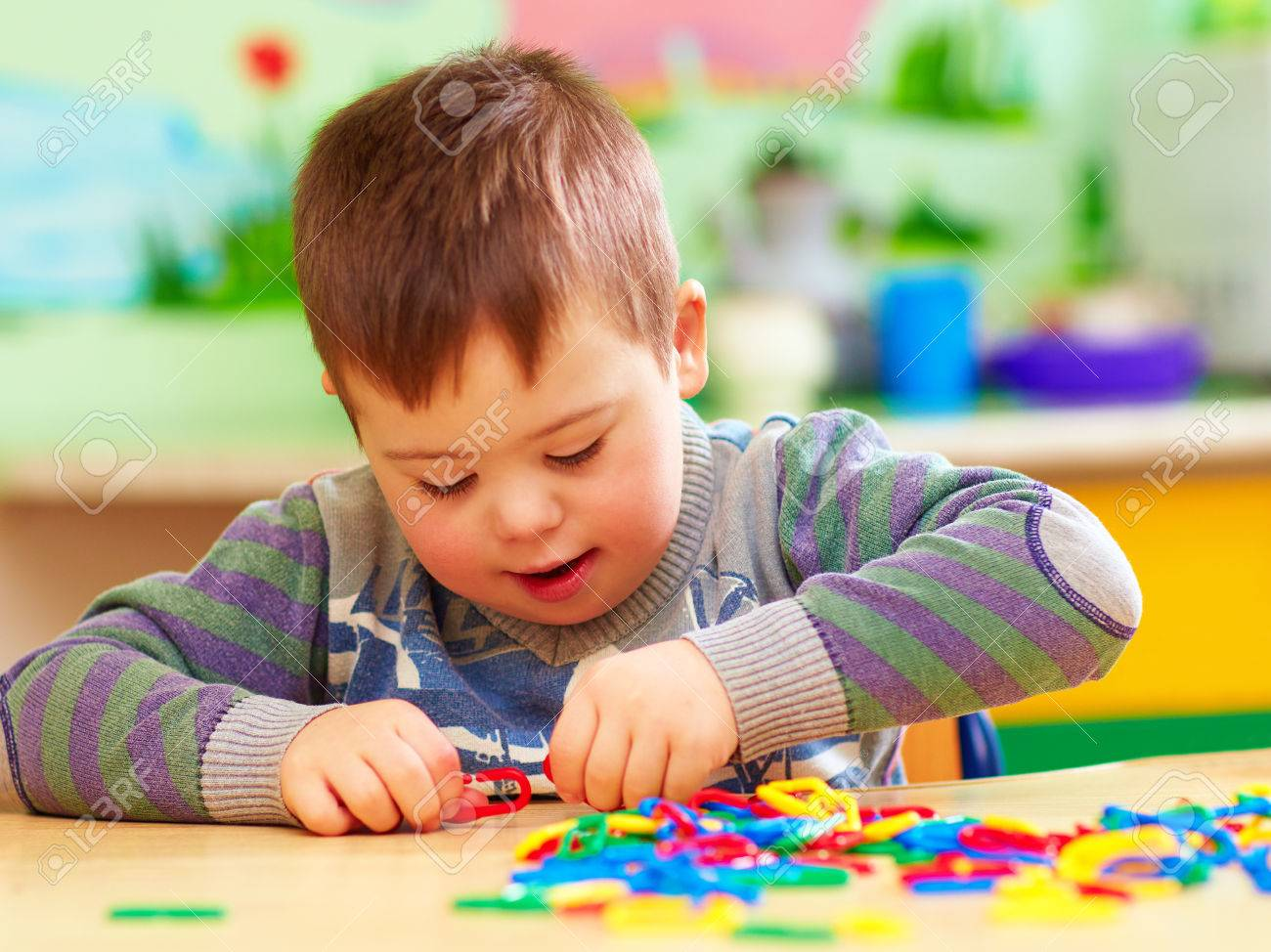 cute kid with down's syndrome playing in kindergarten stock photo