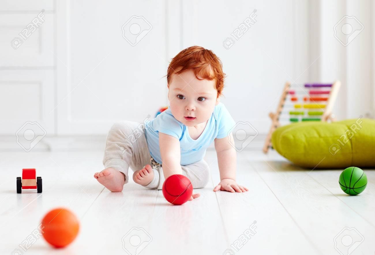 6a6b0b7de Bebé infantil lindo que se arrastra en el suelo en casa, jugando con bolas  de