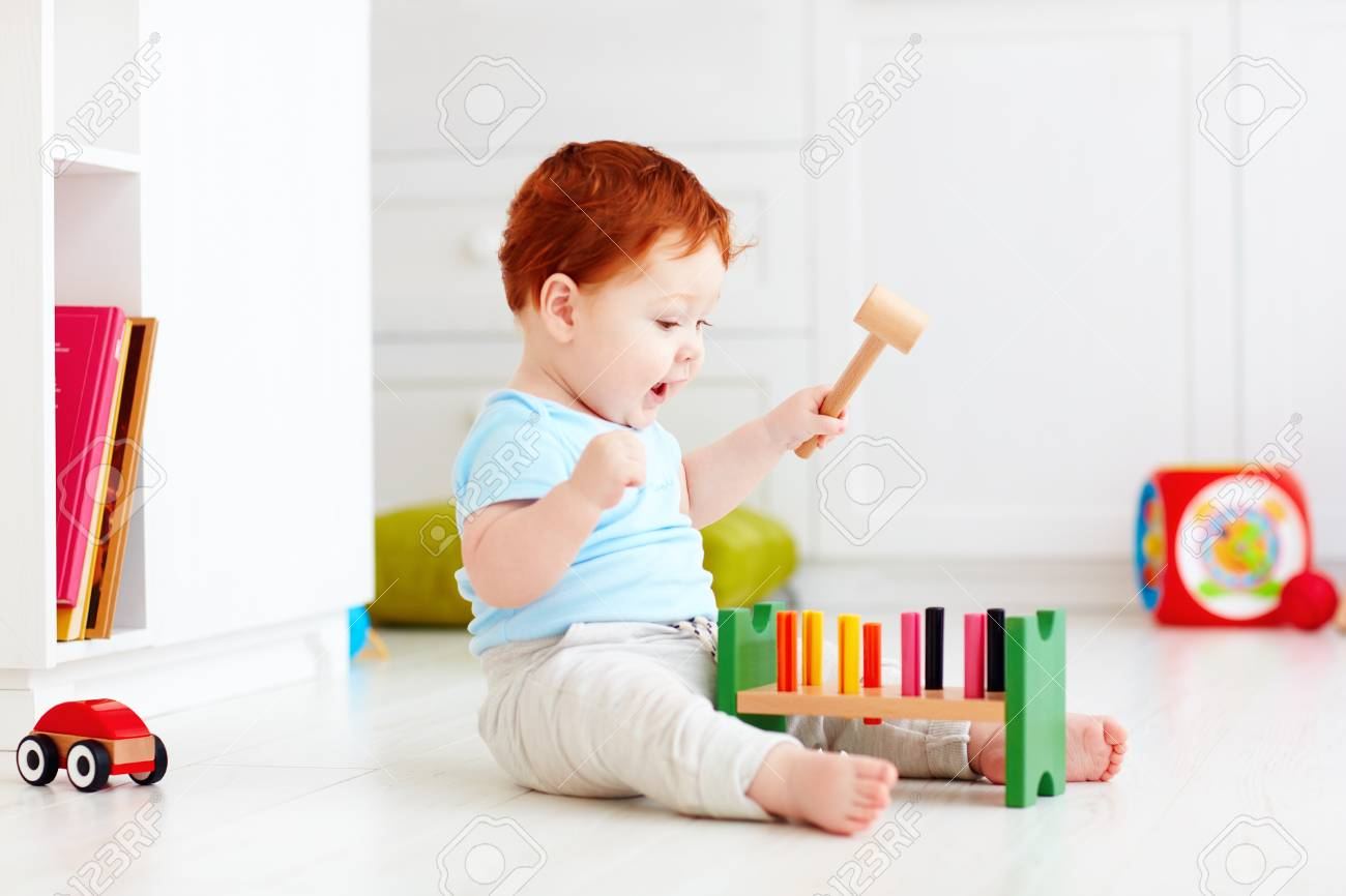cute infant baby playing with wooden hammer block toy - 73253341
