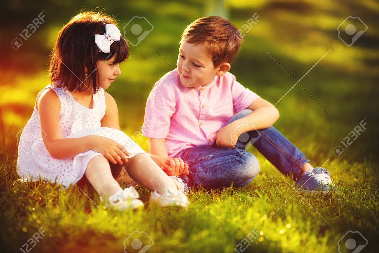 cute kids in love, sitting together in spring garden stock photo