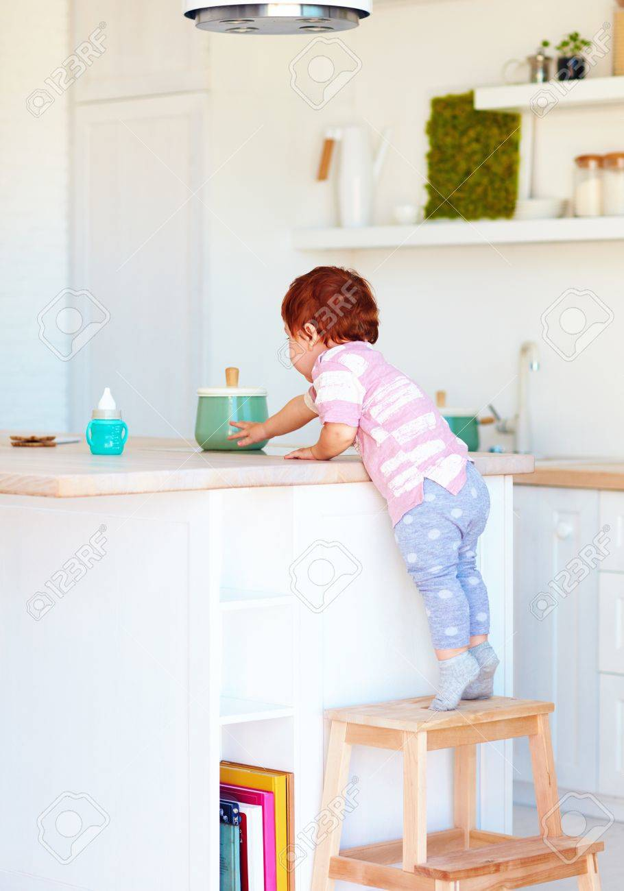 Cute Toddler Baby Climbs On Step Stool, Trying To Reach Things ...