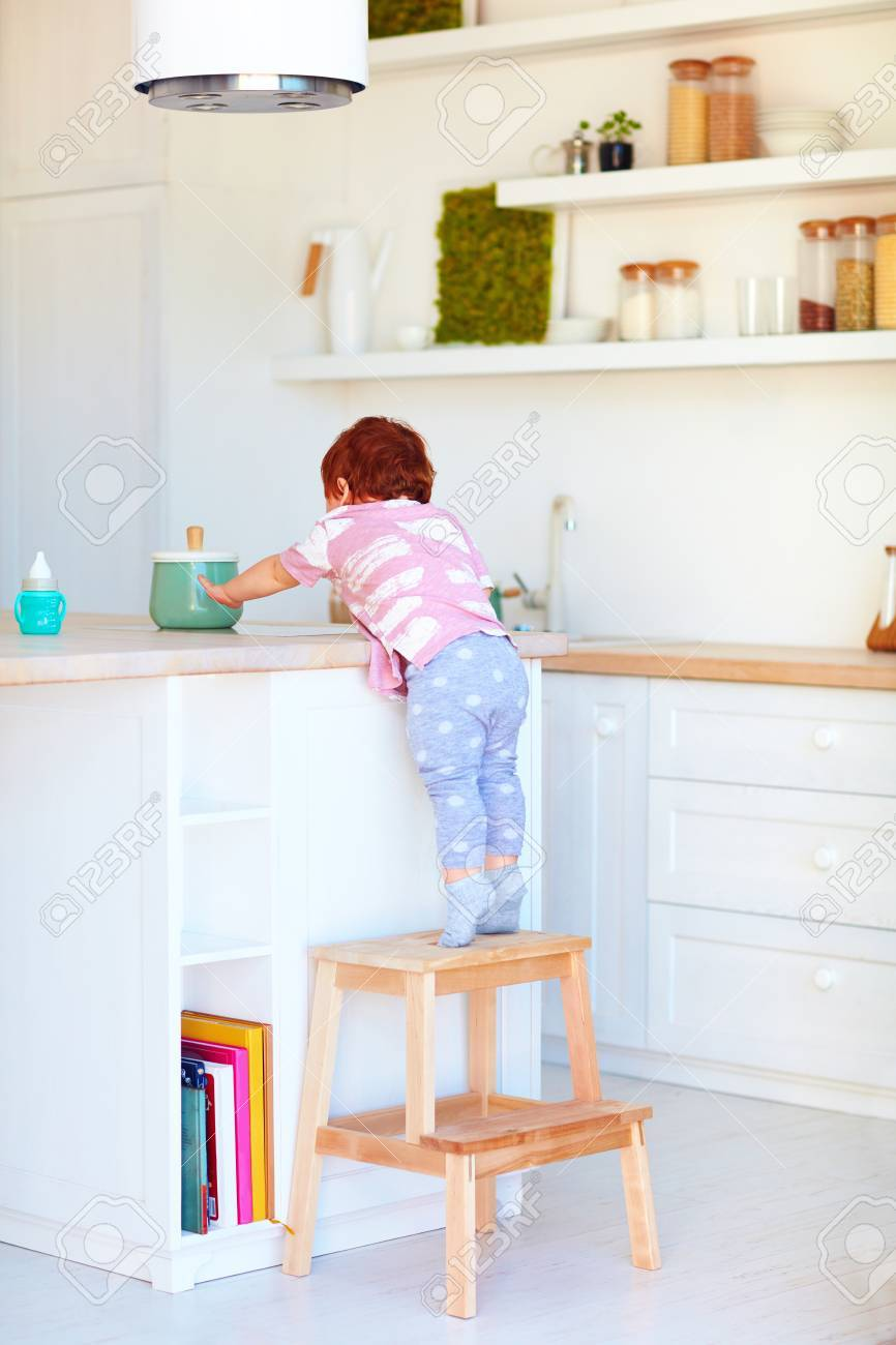 Cute Toddler Baby Climbs On Step Stool, Trying To Reach Things On The High  Desk