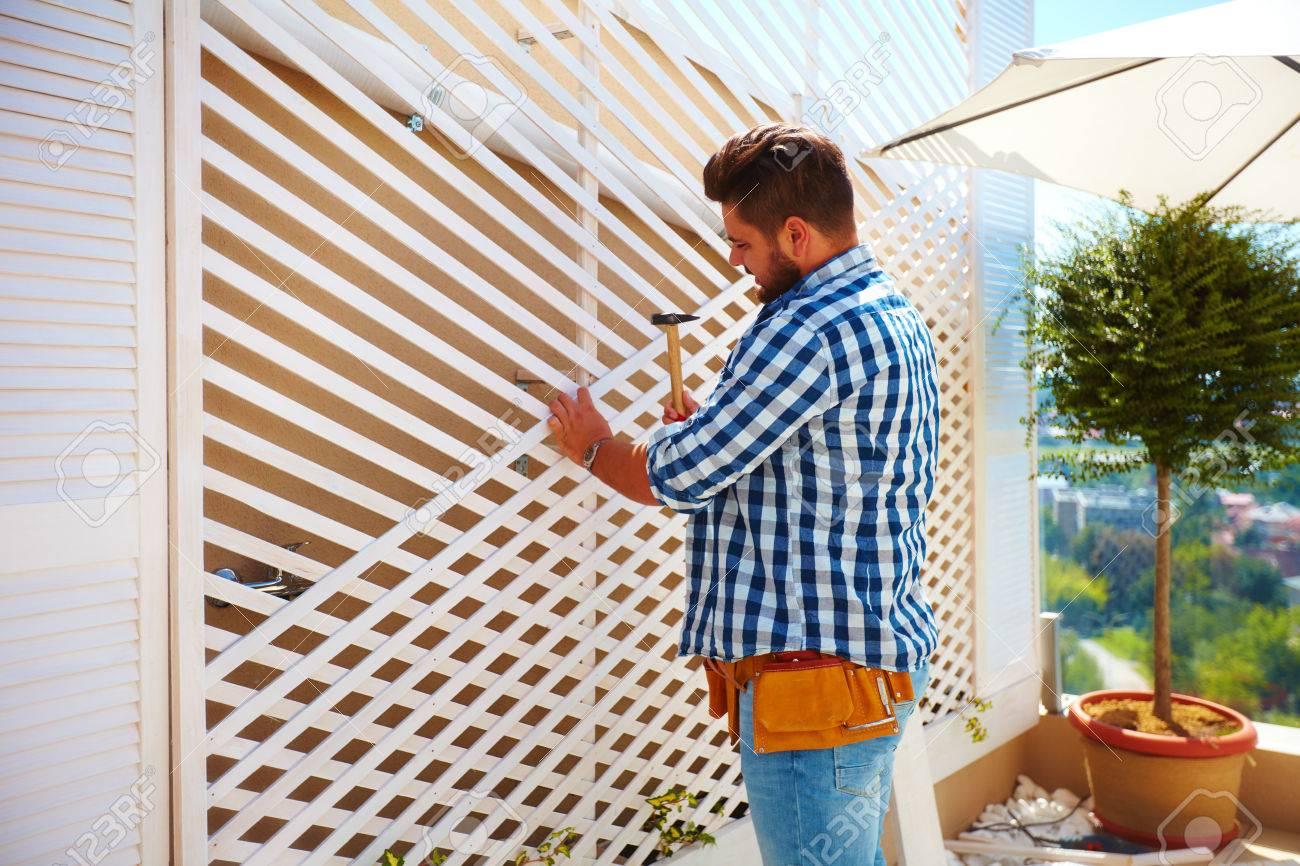 Fabriquer Treillis Bois Pour Plantes Grimpantes jeune homme adulte décorant le mur de la maison, en installant le treillis  en bois pour les plantes grimpantes
