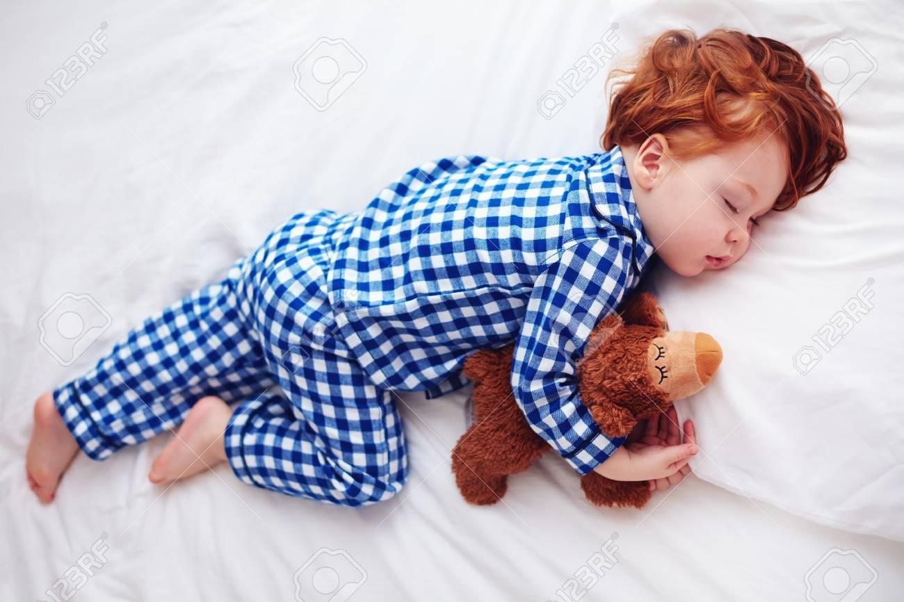 3410ec9ca7 Adorable bebé pelirrojo niño durmiendo con peluche en pijama de franela  Foto de archivo - 91269032