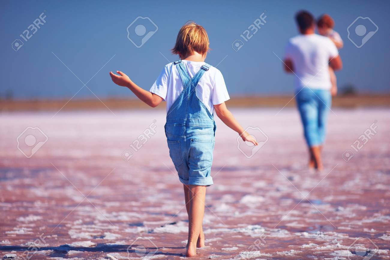 a2afc6a08b18 Stock Photo - young boy in jeans romper walking through the pink salt lake