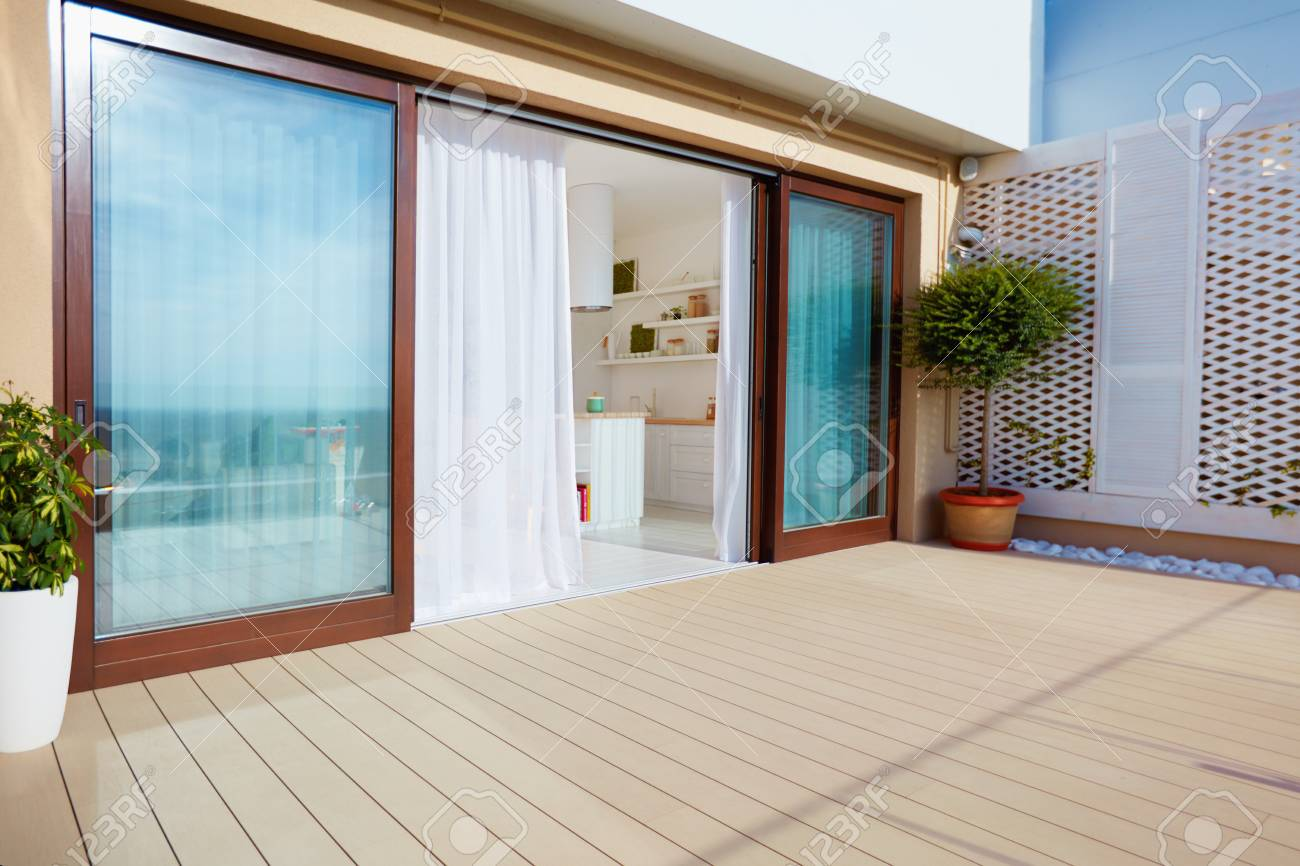 Roof top patio with open space kitchen, sliding doors and decking on upper floor - 92821597