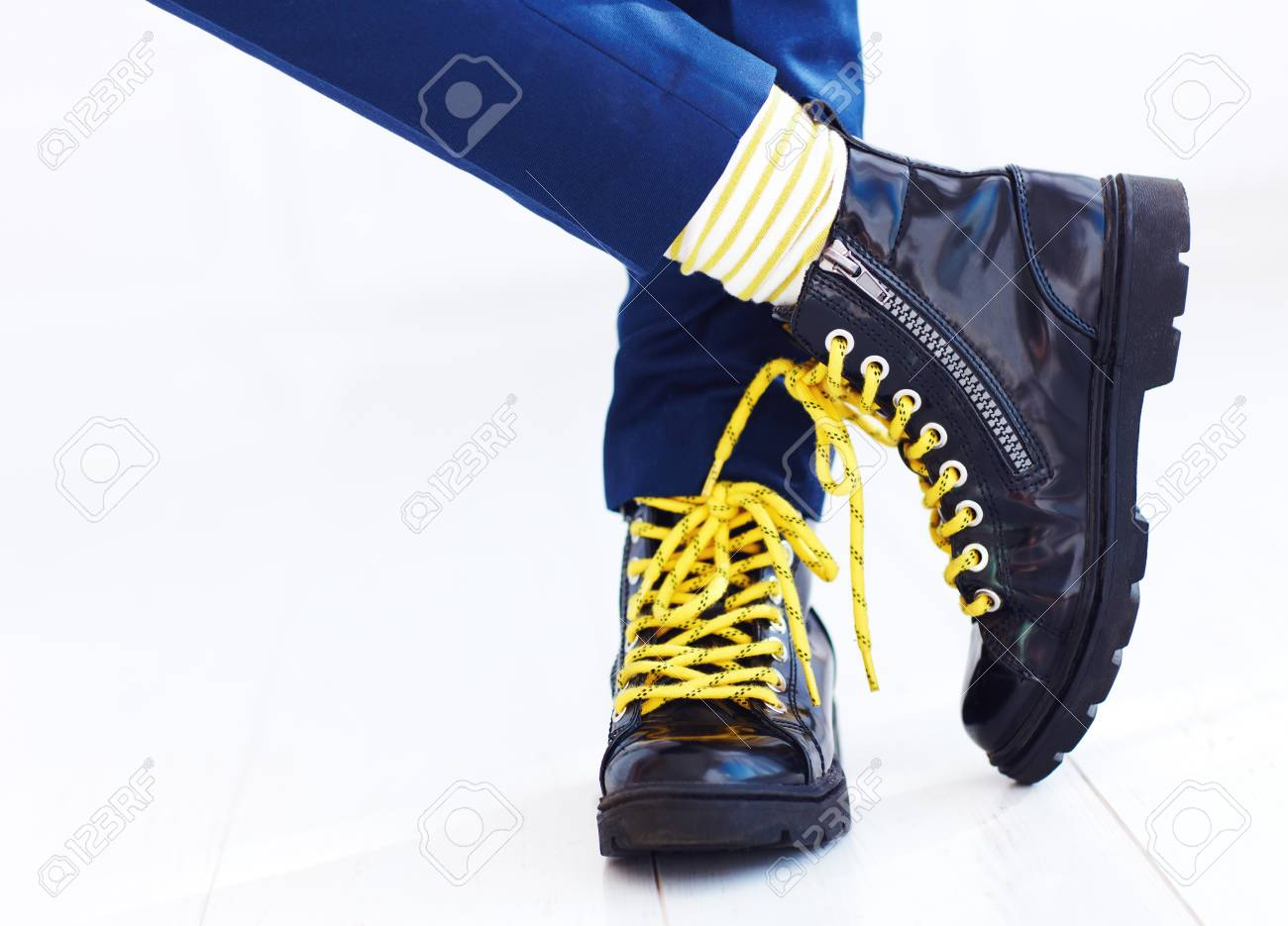 stylish look of patent leather ankle boots with yellow shoelaces..
