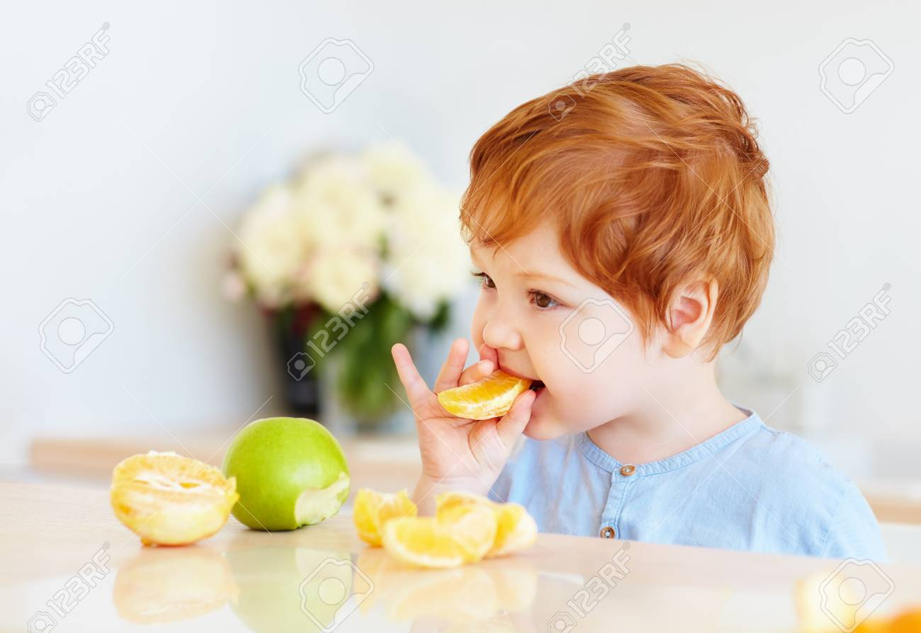 cute redhead toddler baby tasting orange slices and apples at the kitchen - 101733697
