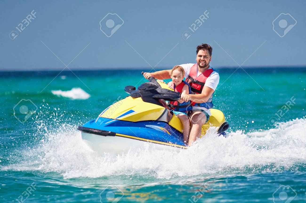 happy, excited family, father and son having fun on jet ski at summer vacation - 105349463