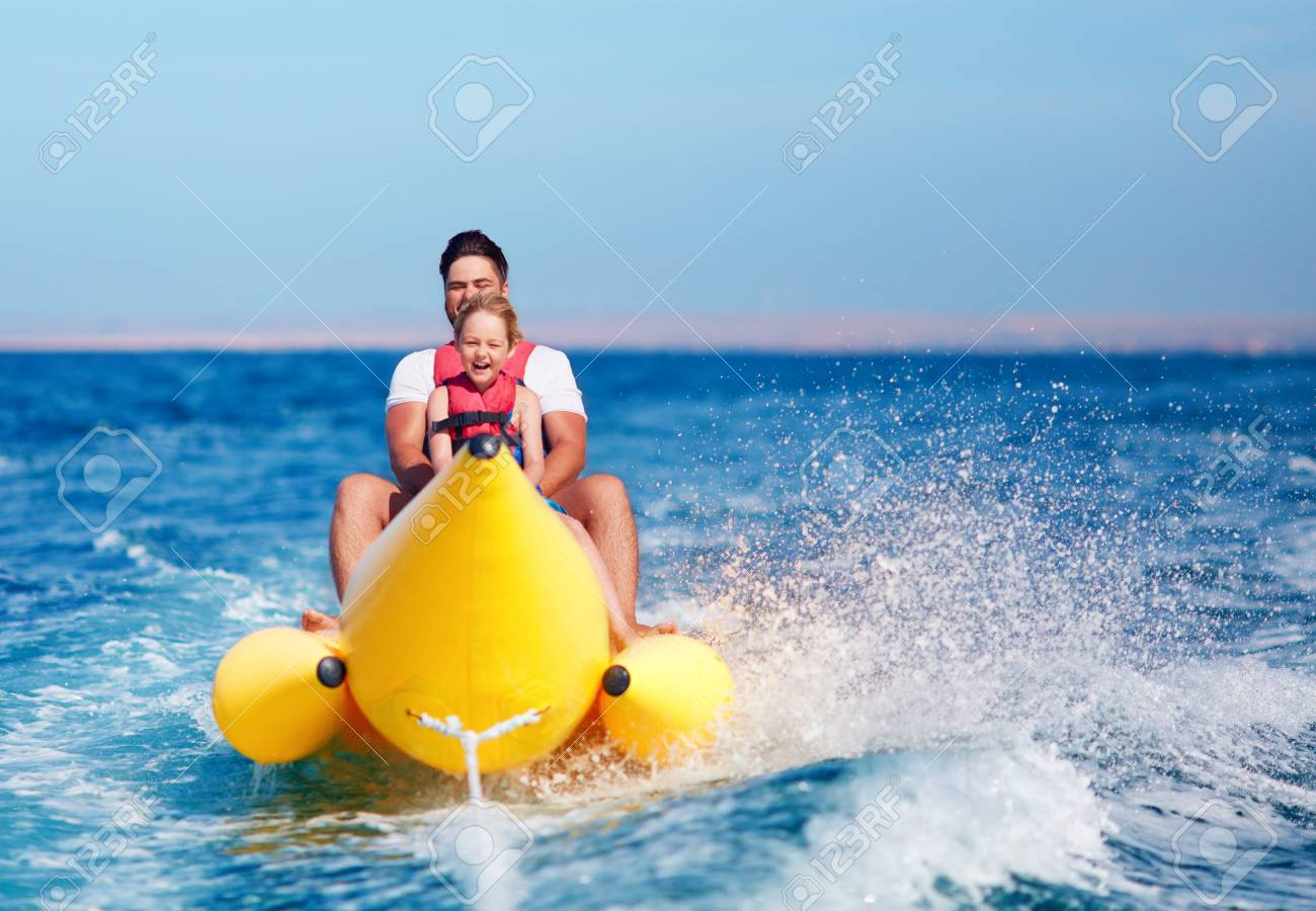 happy family, delighted father and son having fun, riding on banana boat during summer vacation - 104585123