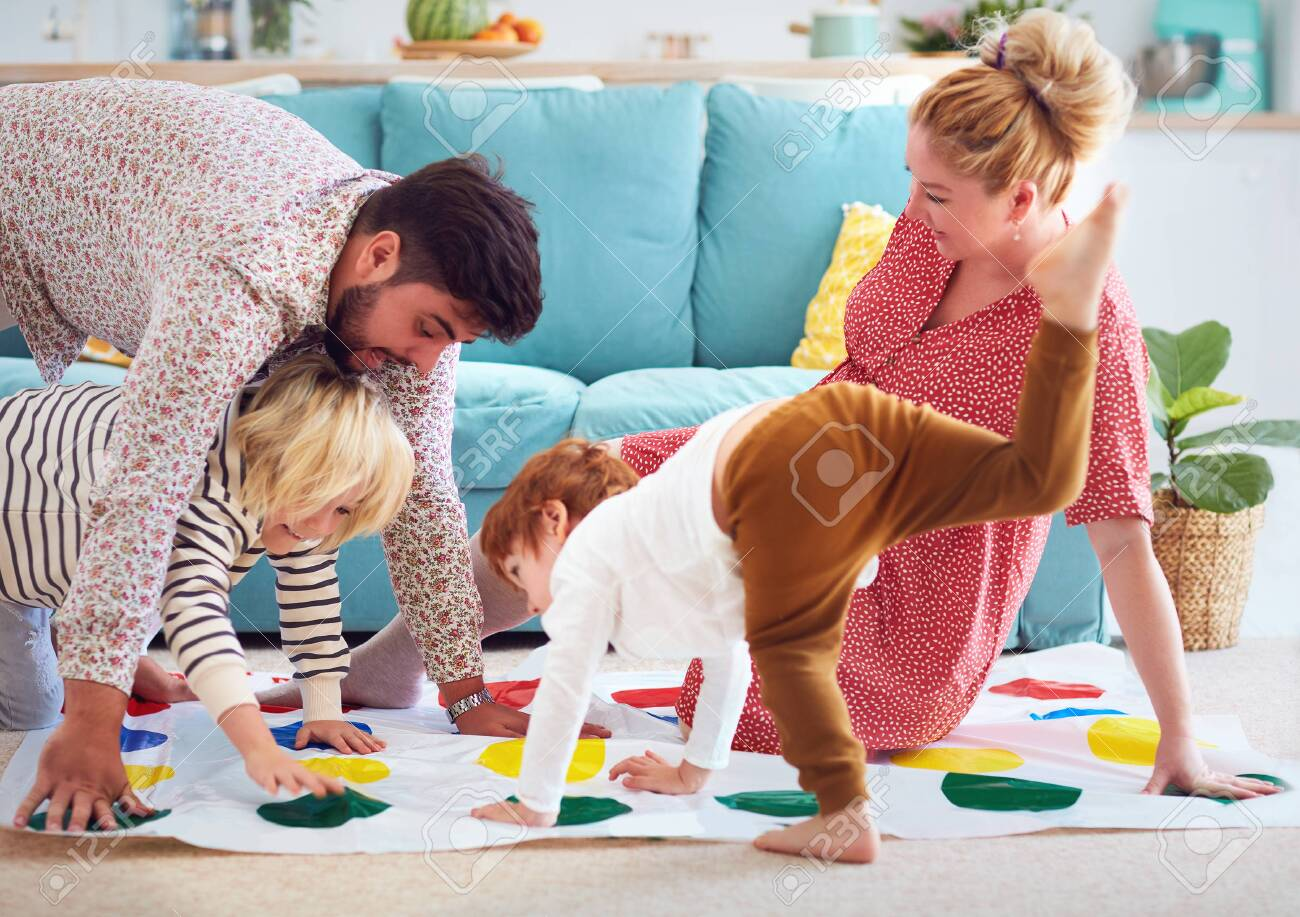 happy family having fun together, playing twister game at home - 131986967