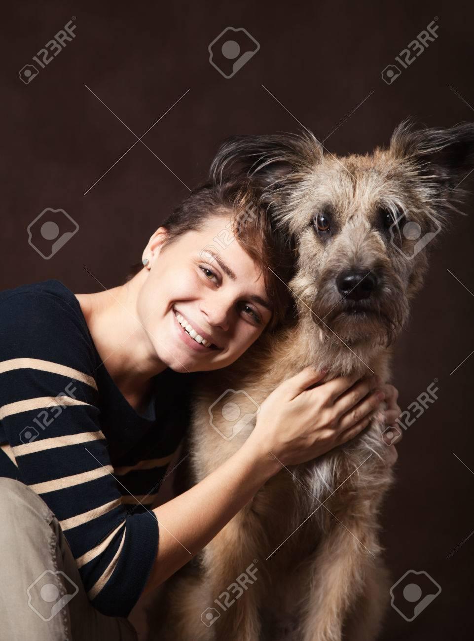 Femme Hirsute Photo belle jeune femme avec un chien hirsute drôle sur un fond sombre. de