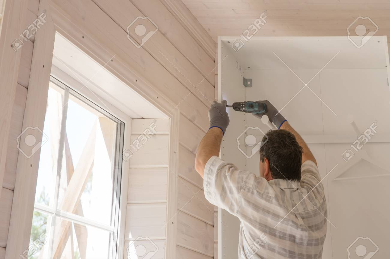 The process of assembling furniture, the master assembles a white cabinet using an electric drill in a room with a white wooden finish - 118805055