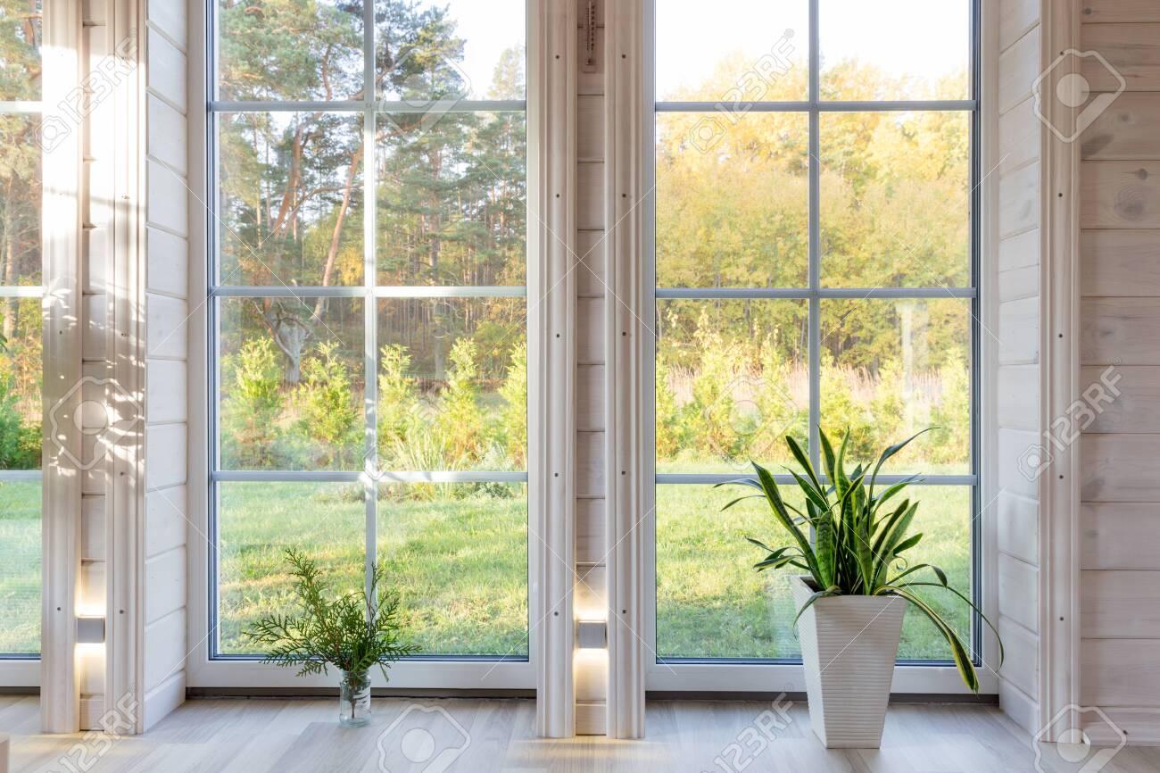 Bright photo studio interior with big window, high ceiling, white wooden floor - 120748756