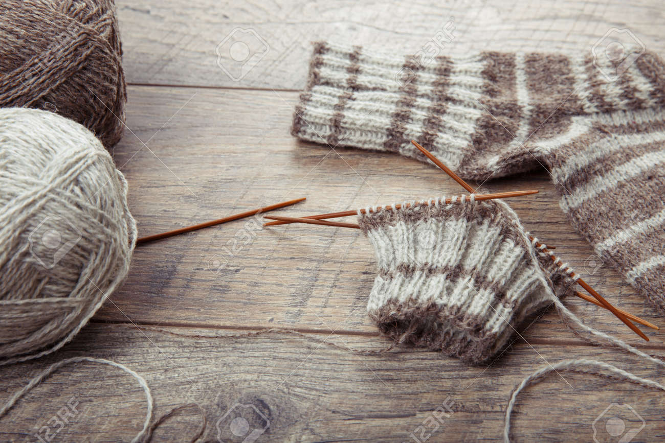 The process of knitting sock with circular bamboo knitting needles, on a wooden rustic table. - 130004779