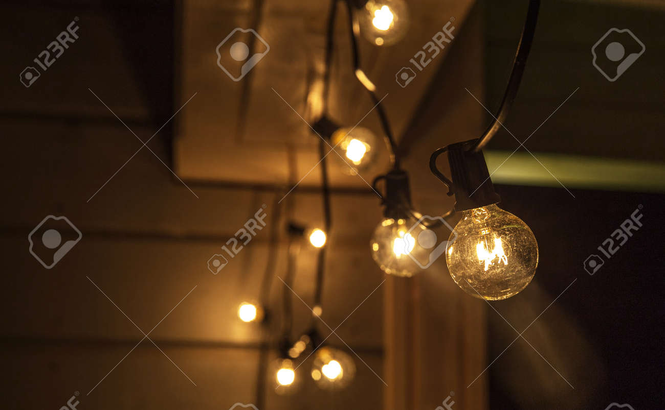 Decorative outdoor string lights hanging on tree in the garden at night time - 165135228