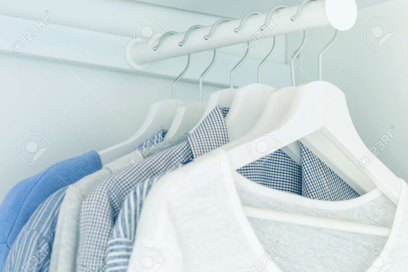 White wardrobe with light blue shirts and blouses hanging on hangers. - 165984044