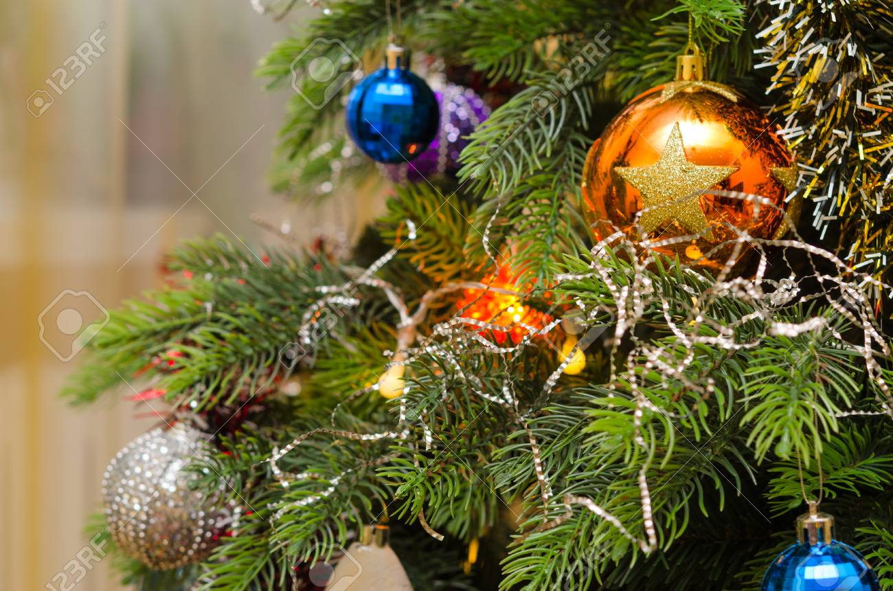 Multi Colored Christmas Balls On Green Branches Of Artificial Holiday Christmas Tree Stock Photo