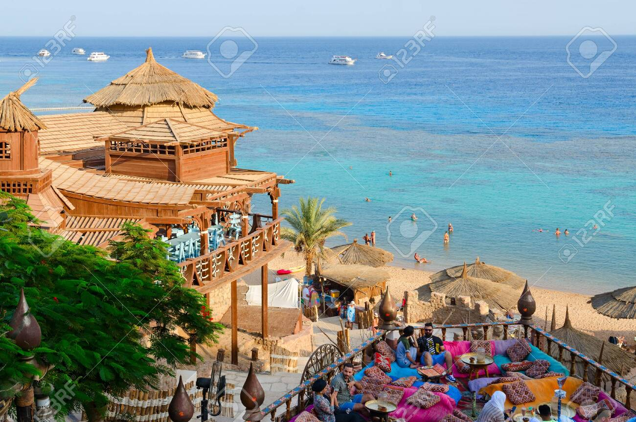 SHARM EL SHEIKH, EGYPT - SEPTEMBER 19, 2019: Unidentified people relax in popular Farsha cafe with original interior on shore of Red Sea in Hadaba district, Sharm El Sheikh, Egypt - 139605241
