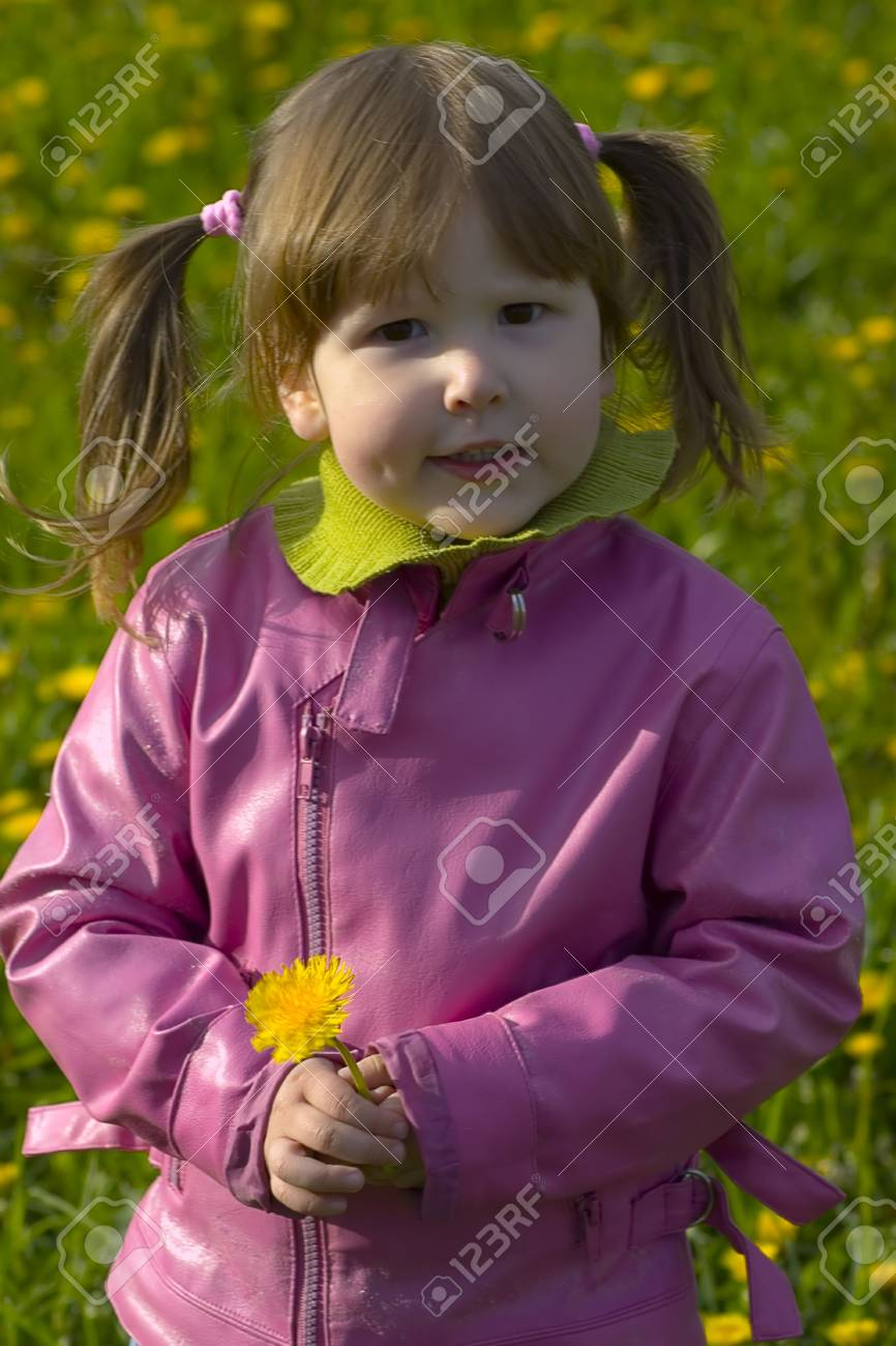 Little girl with dandelion and tails is standing on the field full of dandelions Stock Photo - 923463