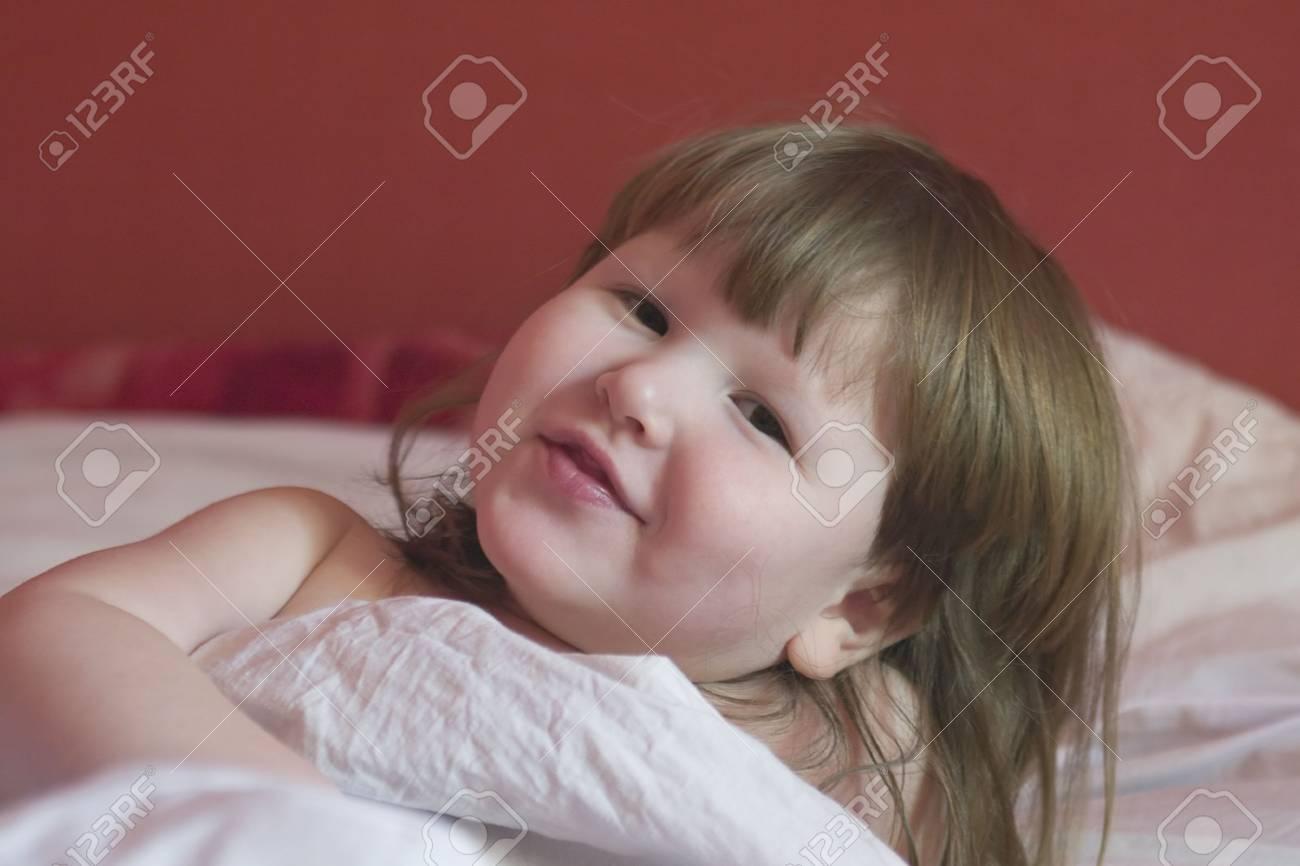 Niña está despertando, viendo usted y sonriente  Foto de archivo - 1117329