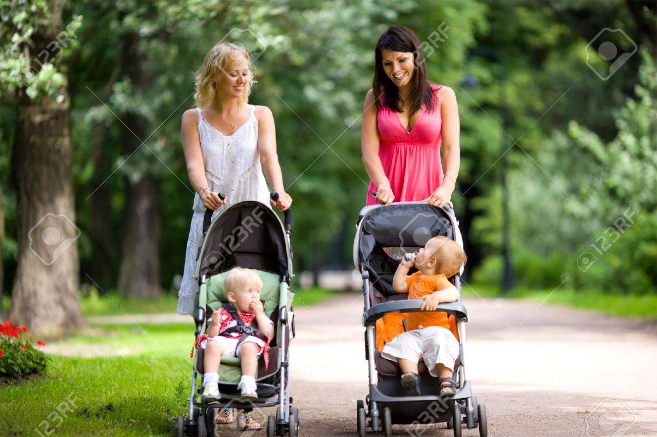 Happy mothers walking together with kids in prams Stock Photo - 5504359