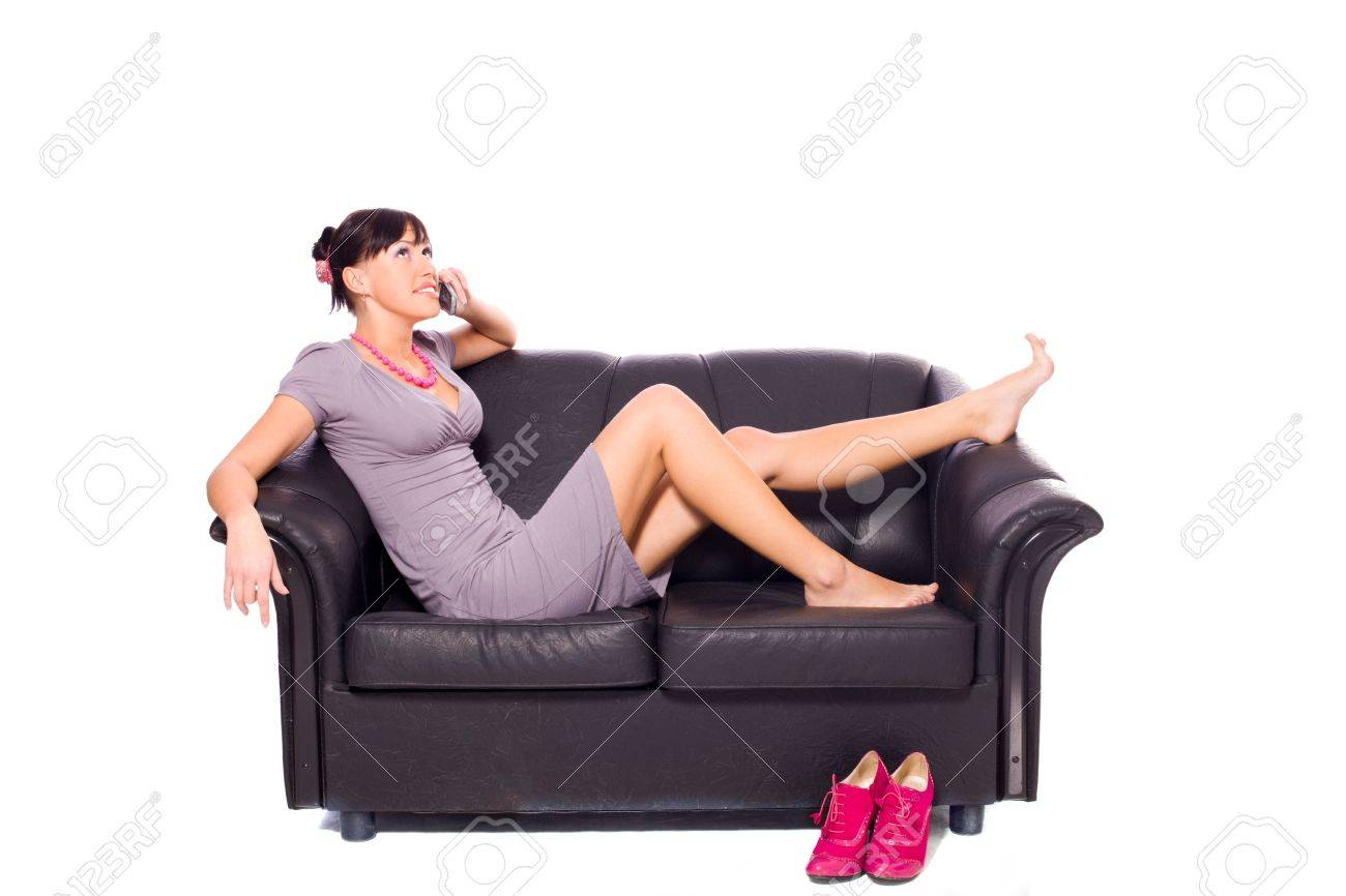 Young woman lying on couch talking on phone isolated on white Stock Photo - 6083298