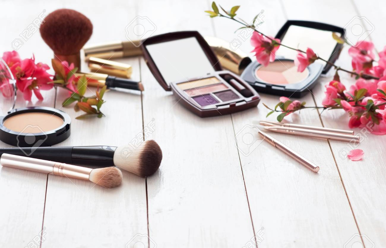 Various cosmetic products for make-up with pink flowers on a white wooden background with copy space. Make-up, lipstick, mascara, eye shadow, powder, brushes - 107864347