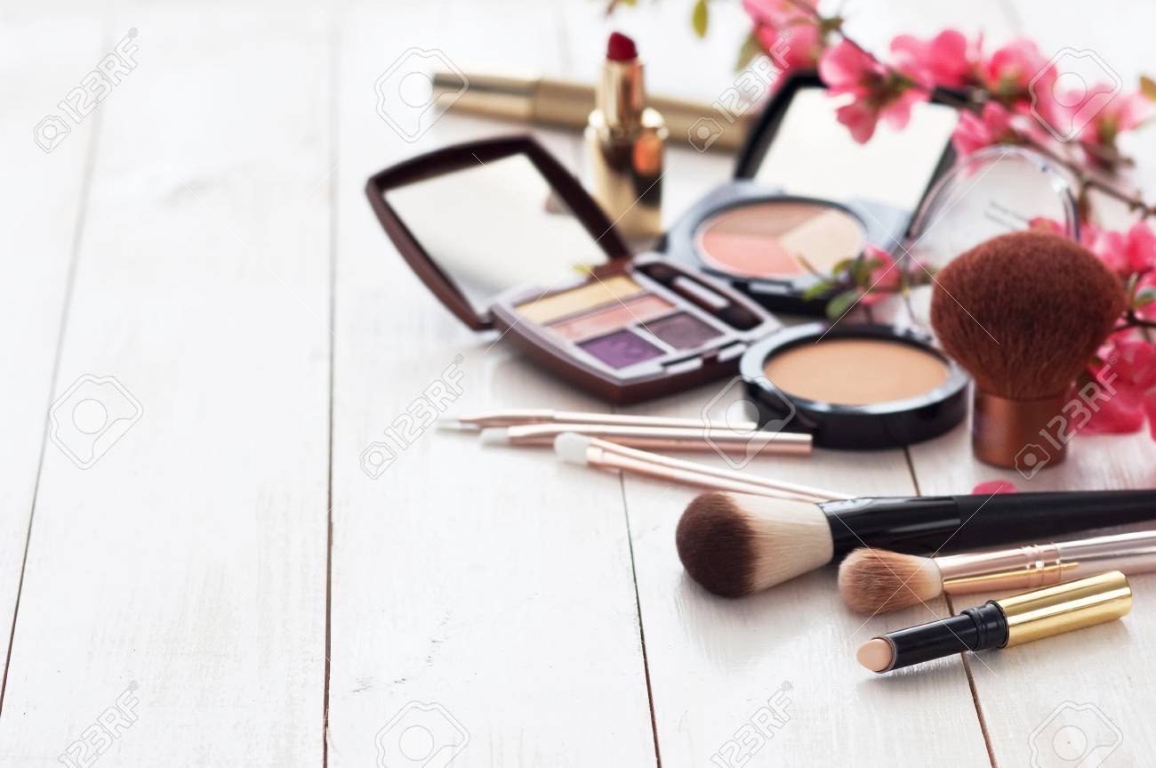 Various cosmetic products for make-up with pink flowers on a white wooden background with copy space. Make-up, lipstick, mascara, eye shadow, powder, brushes - 107864348