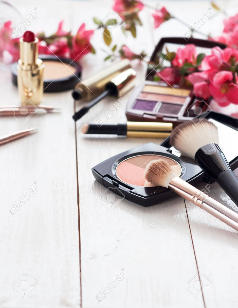 Various cosmetic products for make-up with pink flowers on a white wooden background with copy space. Make-up, lipstick, mascara, eye shadow, powder, brushes - 107864350