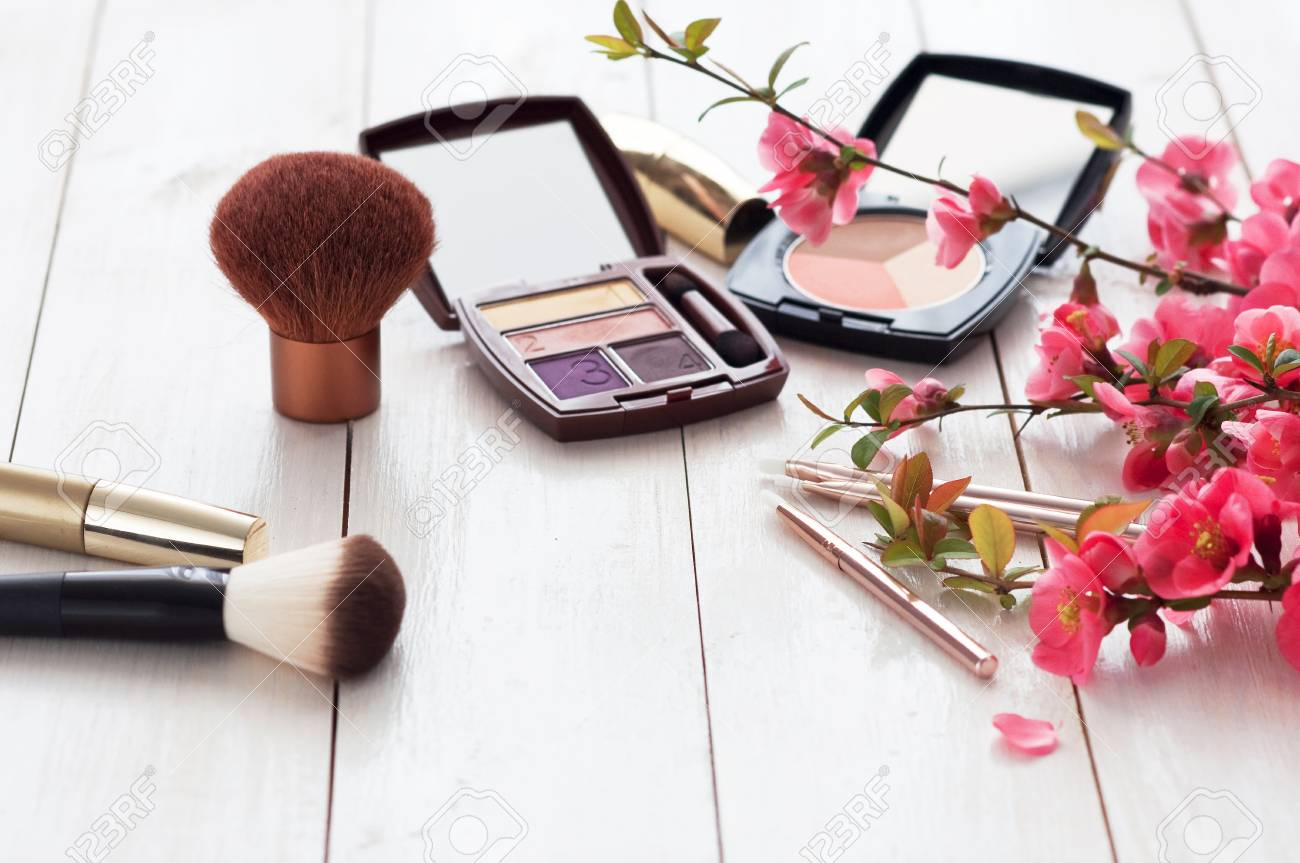 Various cosmetic products for make-up with pink flowers on a white wooden background with copy space. Make-up, lipstick, mascara, eye shadow, powder, brushes - 107864354