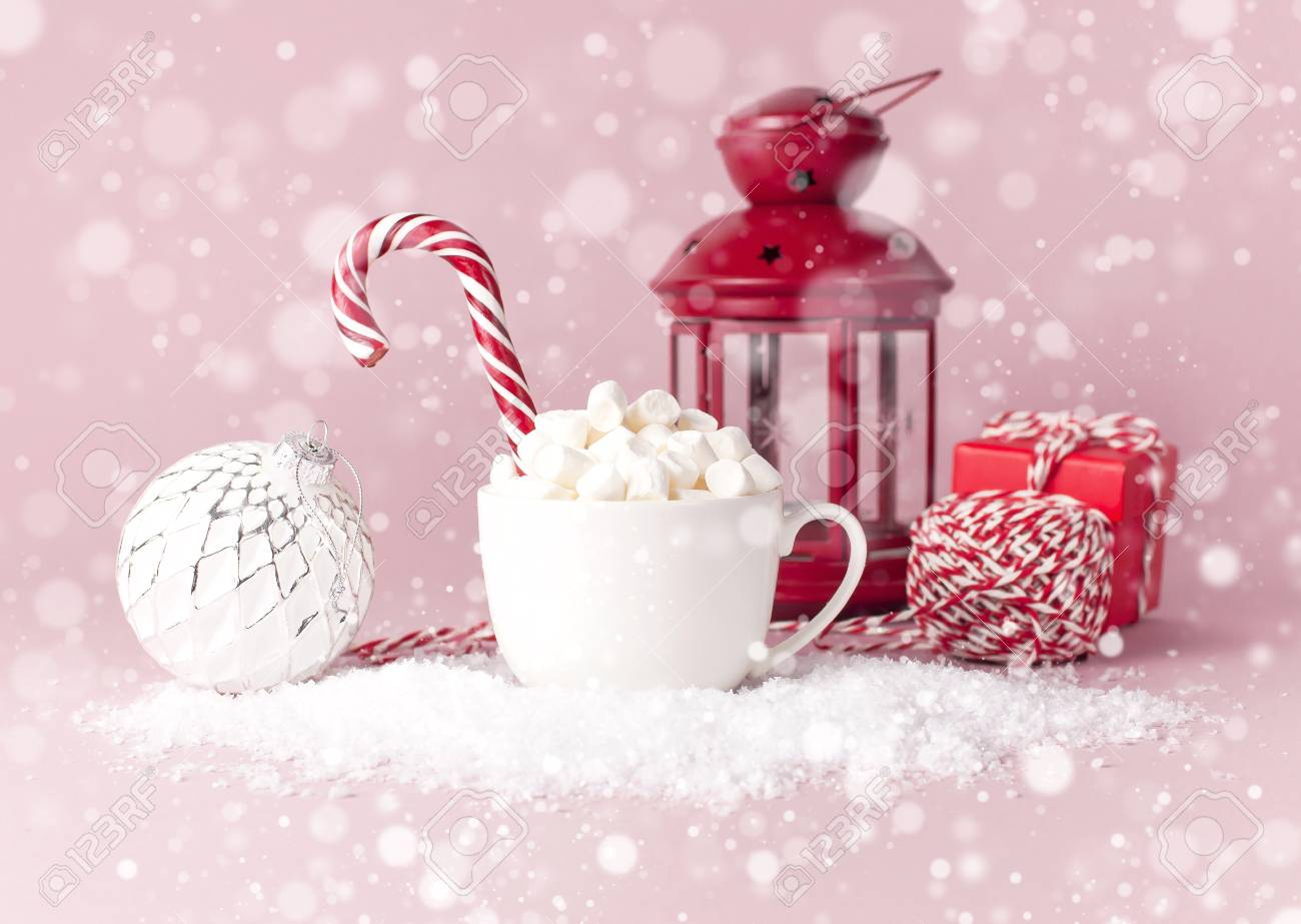White mug with marshmallows Candy Cane gifts boxes Christmas New Year ball packaging lace flashlight in the snow on pink background Flat Lay. Winter traditional drink food Festive decor celebration - 112014396