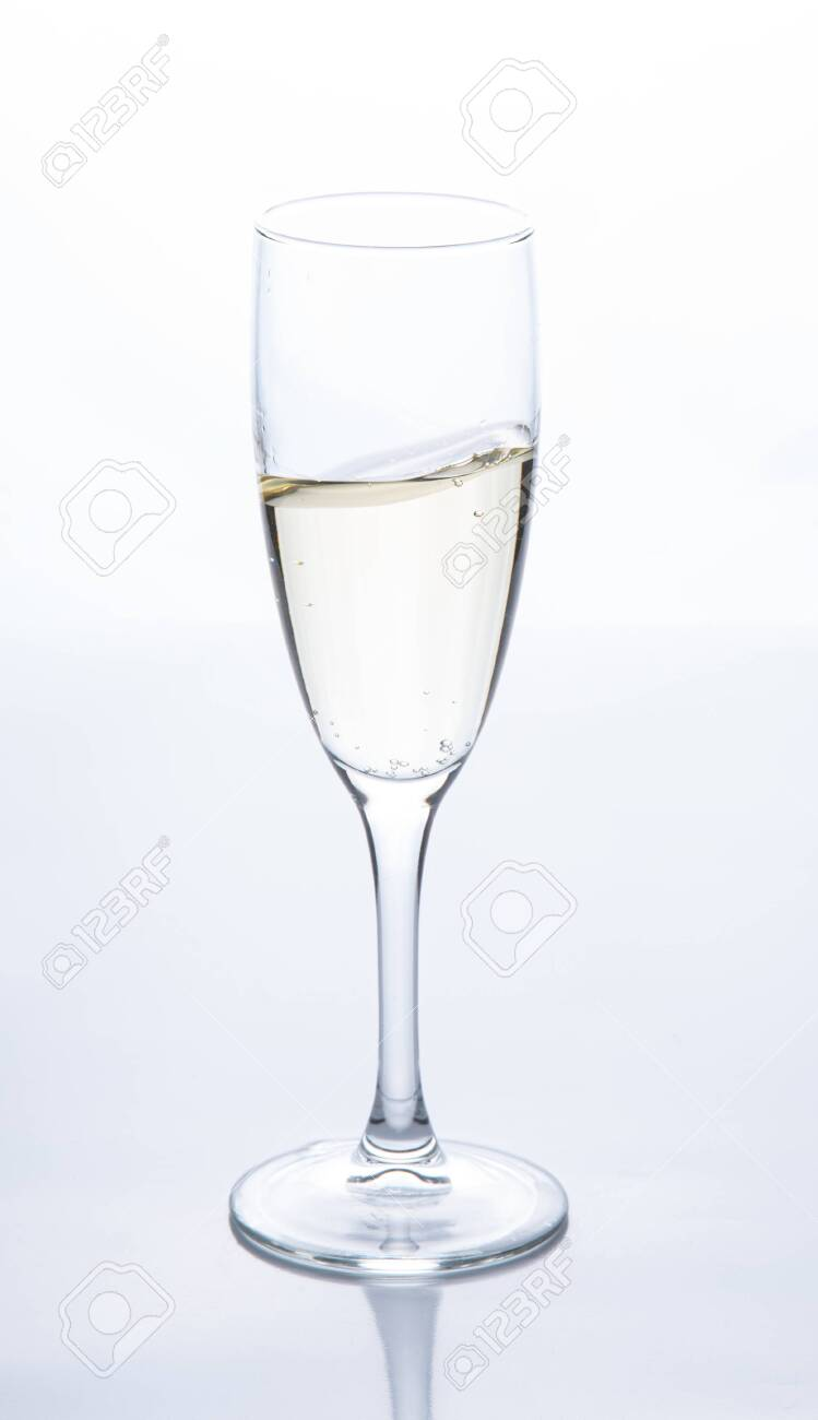 a glass of sparkling champagne is on the table. Contour light. Front view - 137271276