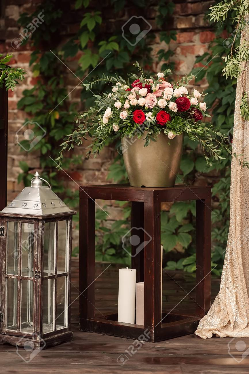 Lampara De Vela Con Un Ramo De Flores Rojas Y Blancas Fotos