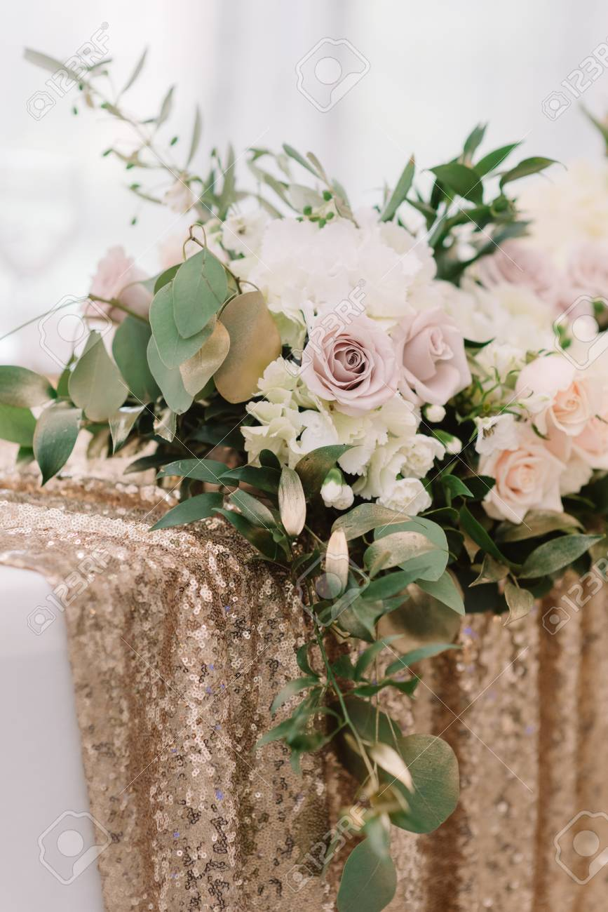 It Is A Lot Of Wedding Flowers On A Table With A Golden Cloth