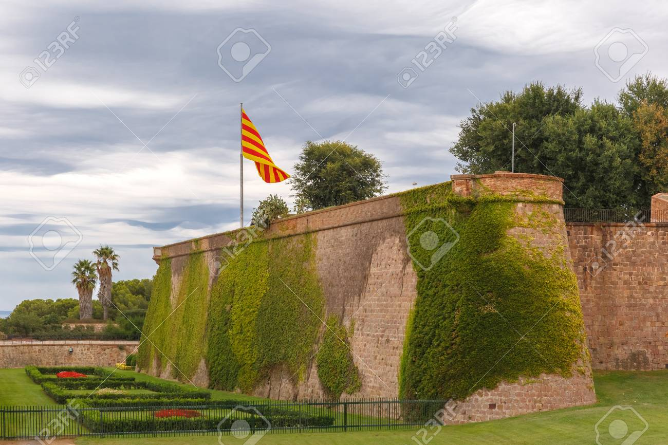 Flag Of Catalonia Over Montjuic Castle, Old Military Fortress On Top Of  Montjuic Hill In