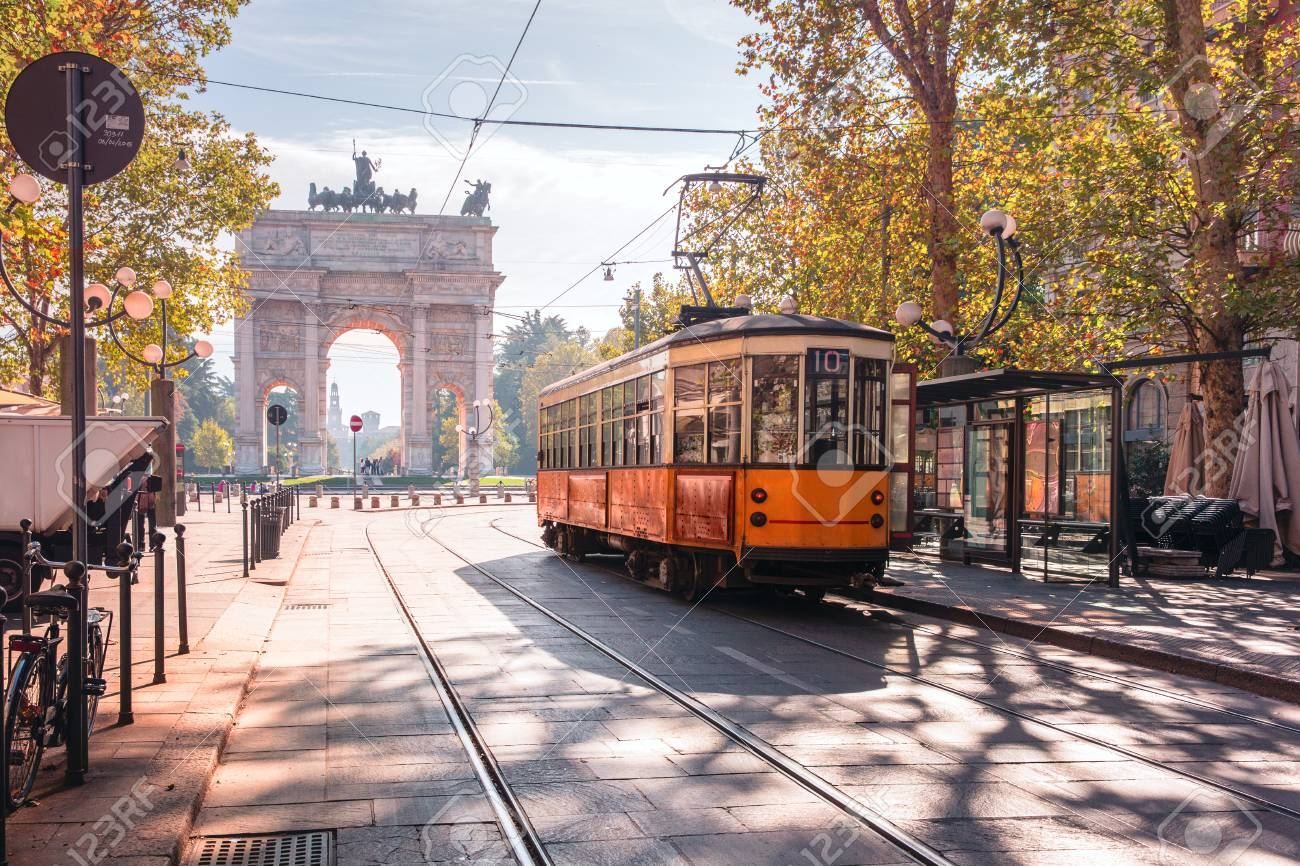 Famous vintage tram in the centre of the Old Town of Milan in the sunny day, Lombardia, Italy. Arch of Peace, or Arco della Pace on the background. - 95010246