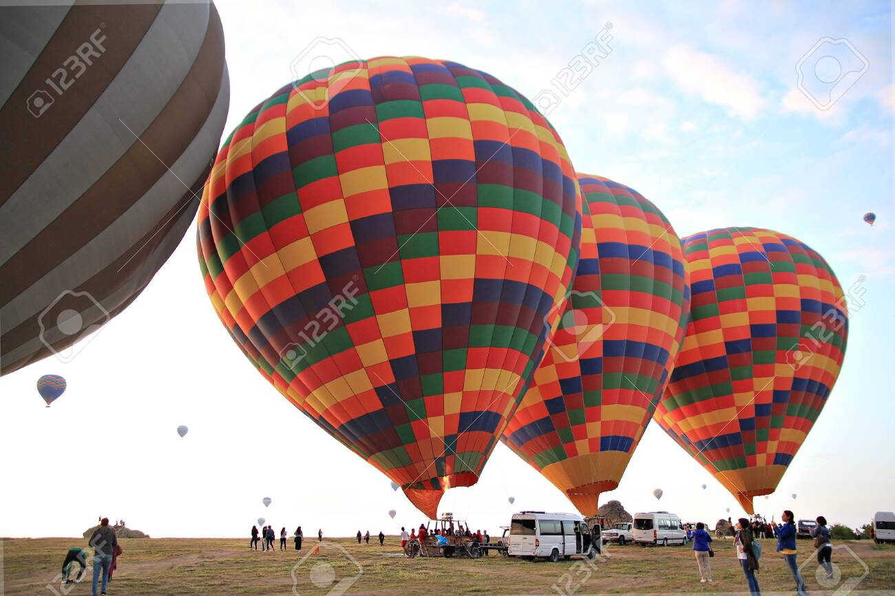 Preparing for take-off hot air balloons with tourists on sunrise - 142602665
