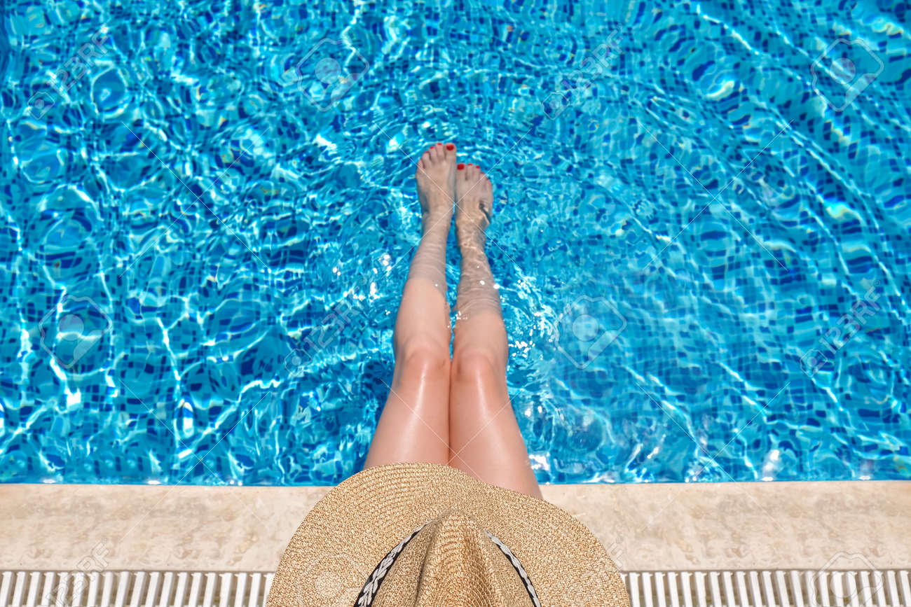Young woman in straw hat sunbathing sitting on the edge of swimming pool with legs in water. top view - 155057668