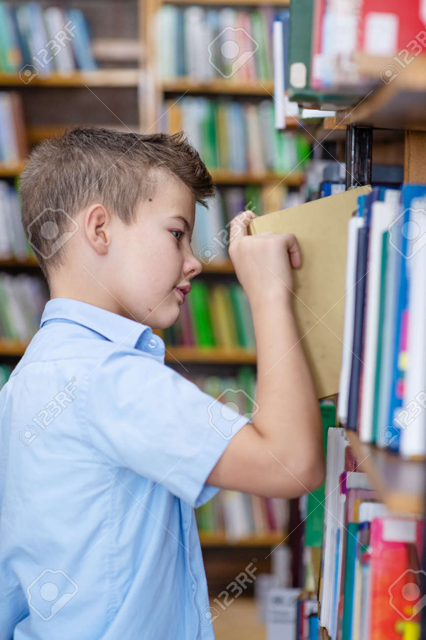 A boy in a blue shirt in a library takes a book from a bookshelf - 157471616