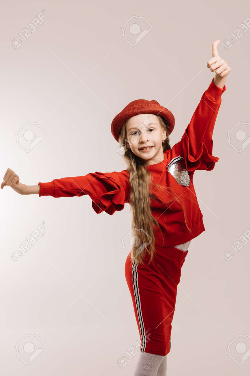 Little girl in a red suit and hat posing on a light background - 148065643
