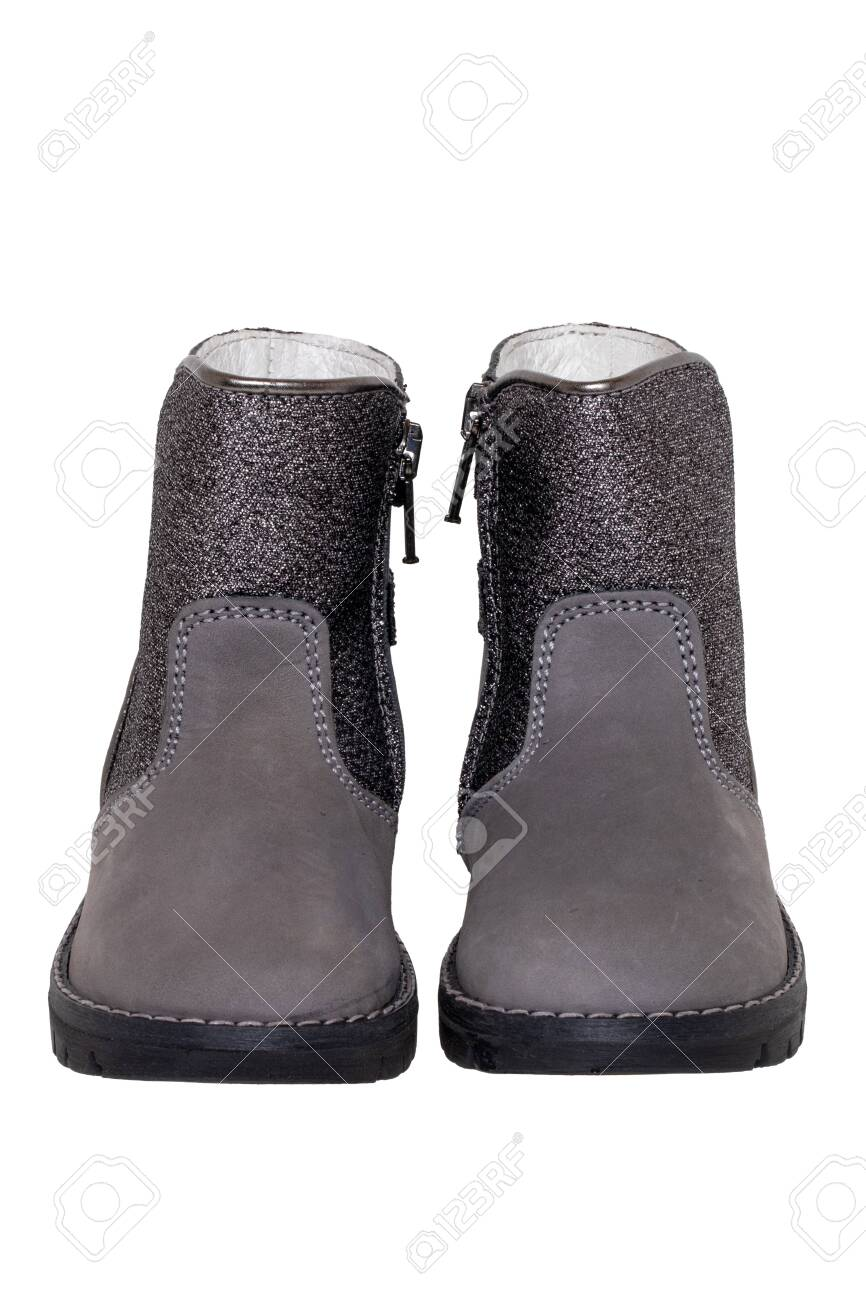 Winter boots. Close-up of a pair elegant gray silver leather winter boots lined with white leather. Girls winter shoe fashion new trends isolated on a white background. Macro photograph. - 136261234