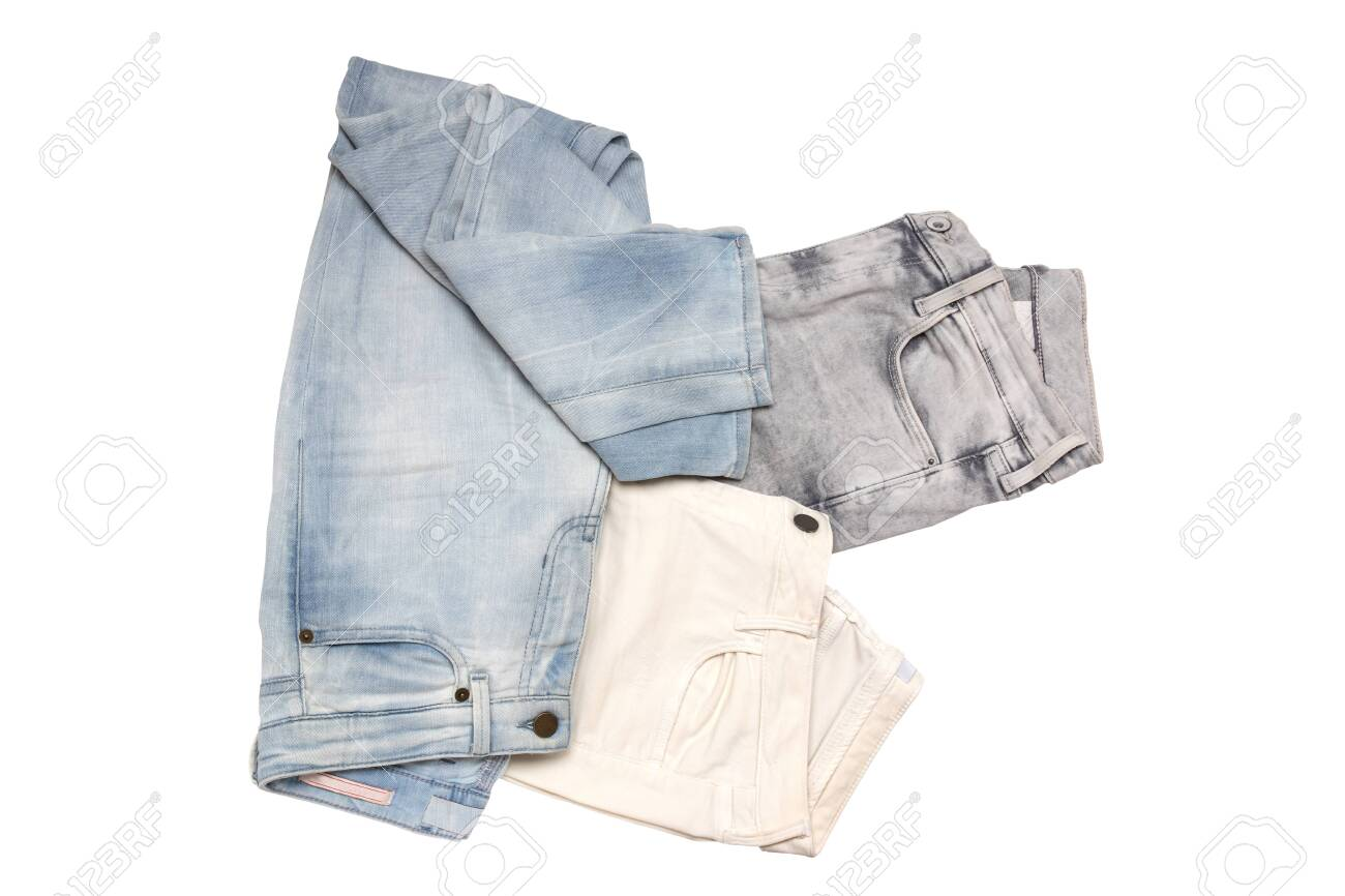 Jeans fashion. Closeup of collection of three female various denim pants or colorful jeans trousers isolated on a white background. Top view flat lay. - 136915477