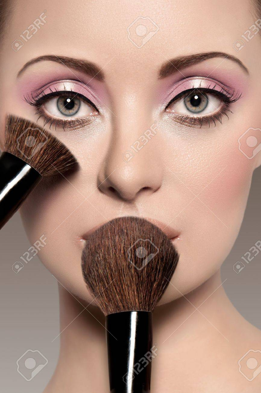 Portrait of a beautiful woman with a make up brush Stock Photo - 10018233