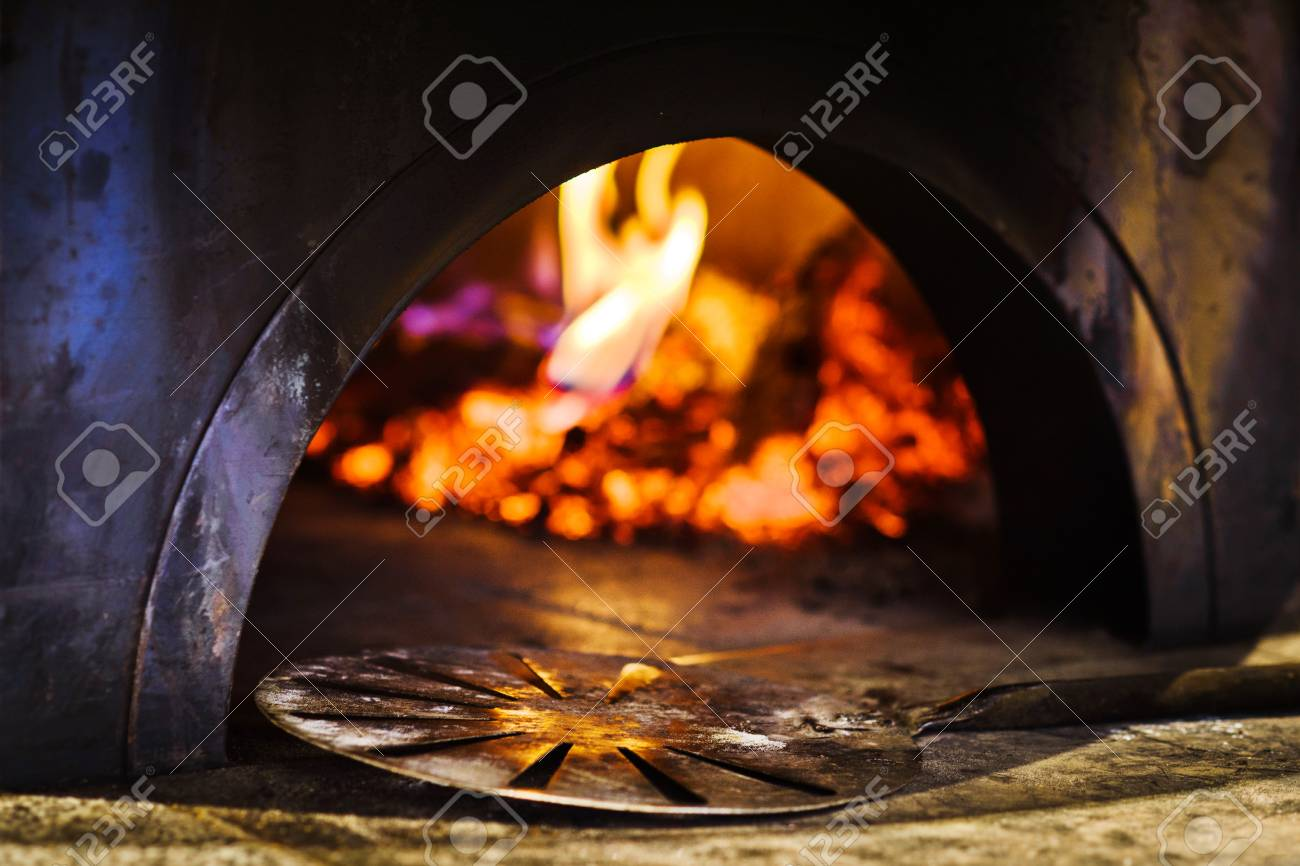 Shovel in front of traditional italian brick pizza oven - 118886590