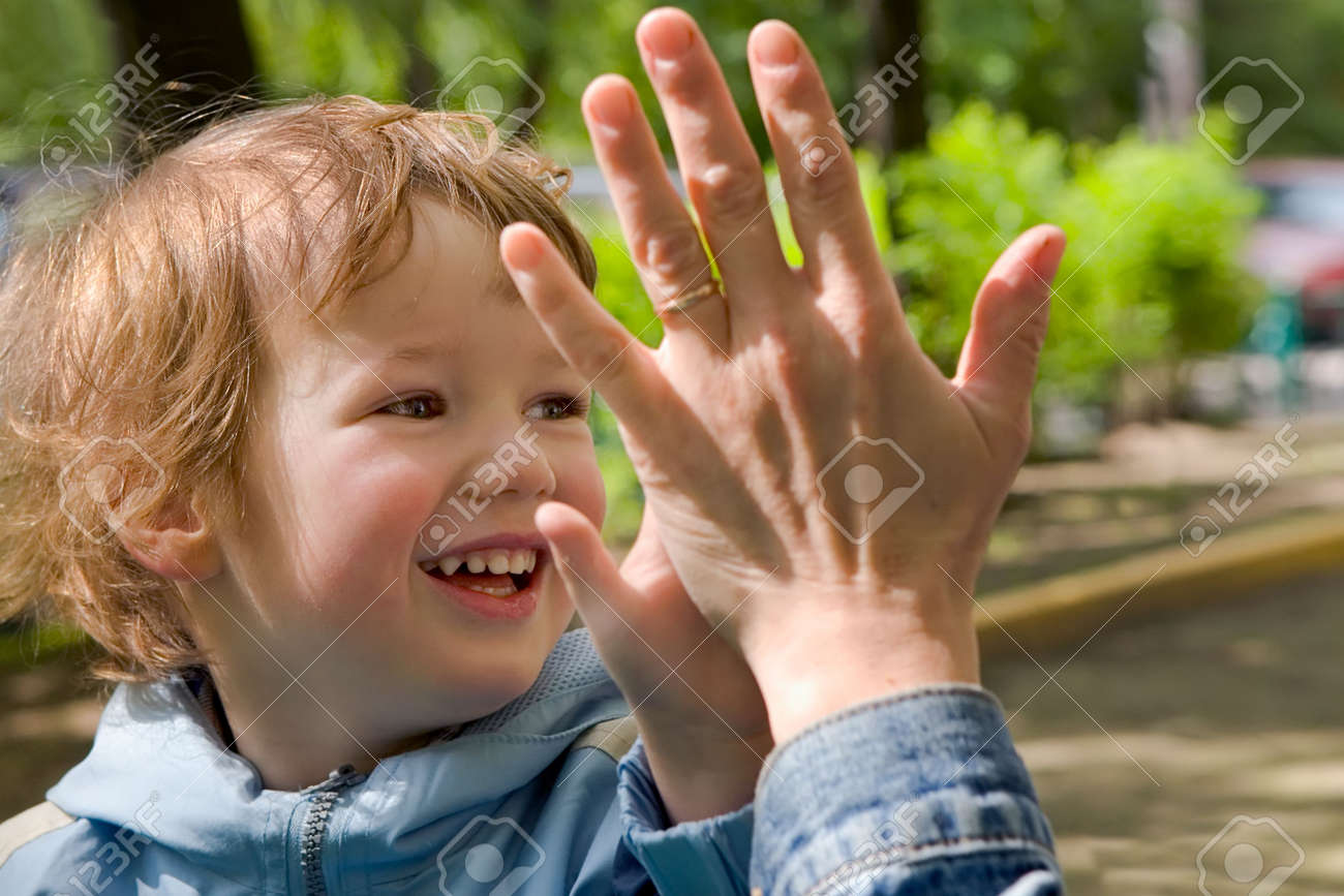 Child cheerfully plays with gentle and kind hands of mum Stock Photo - 590775