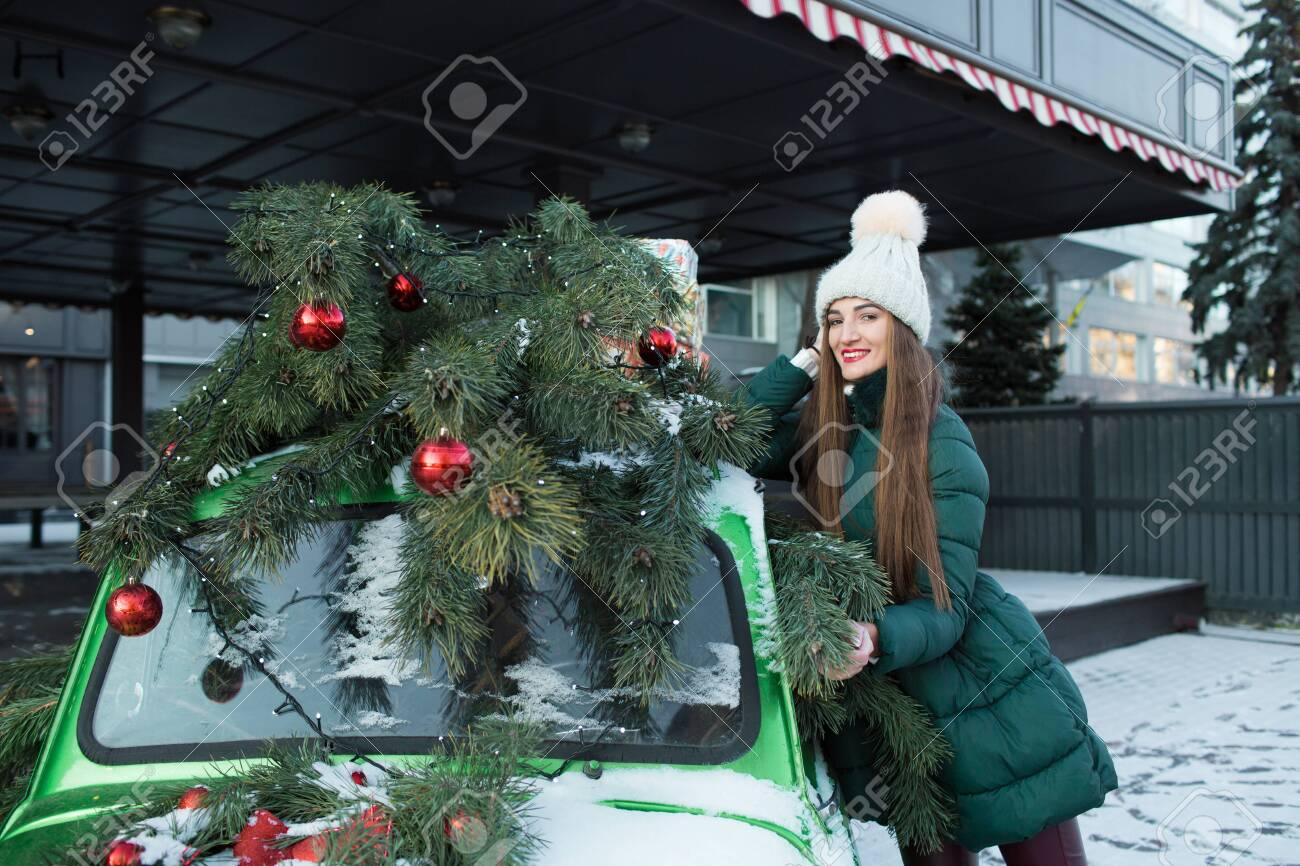 Girl in winter green clothes on the street, near a green retro car. Beautiful happy woman with gift box at celebration party. Christmas and New Year holidays. - 132270253